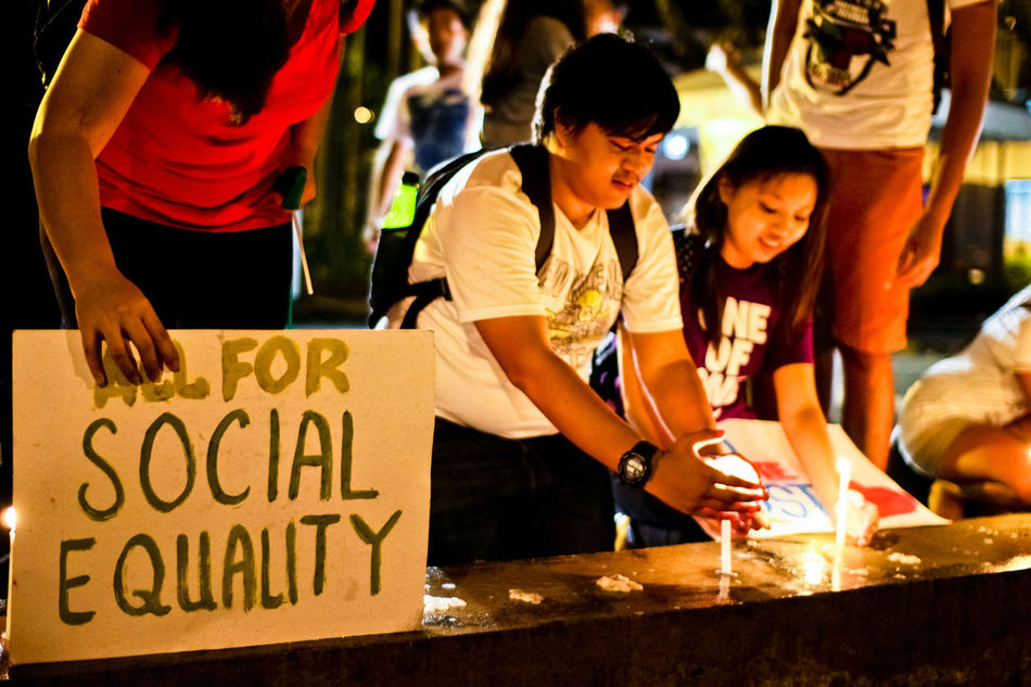 Member of a youth group, inside a university in the Philippines, light candles during a rally calling for social equality. CHRIS QUINTANA Adult ASIA Equality Equality For All Friendship GenderEquality Happiness Night Outdoors People Social Issues Society Text Togetherness Young Adult Young Women Youth Culture Youth Of Today