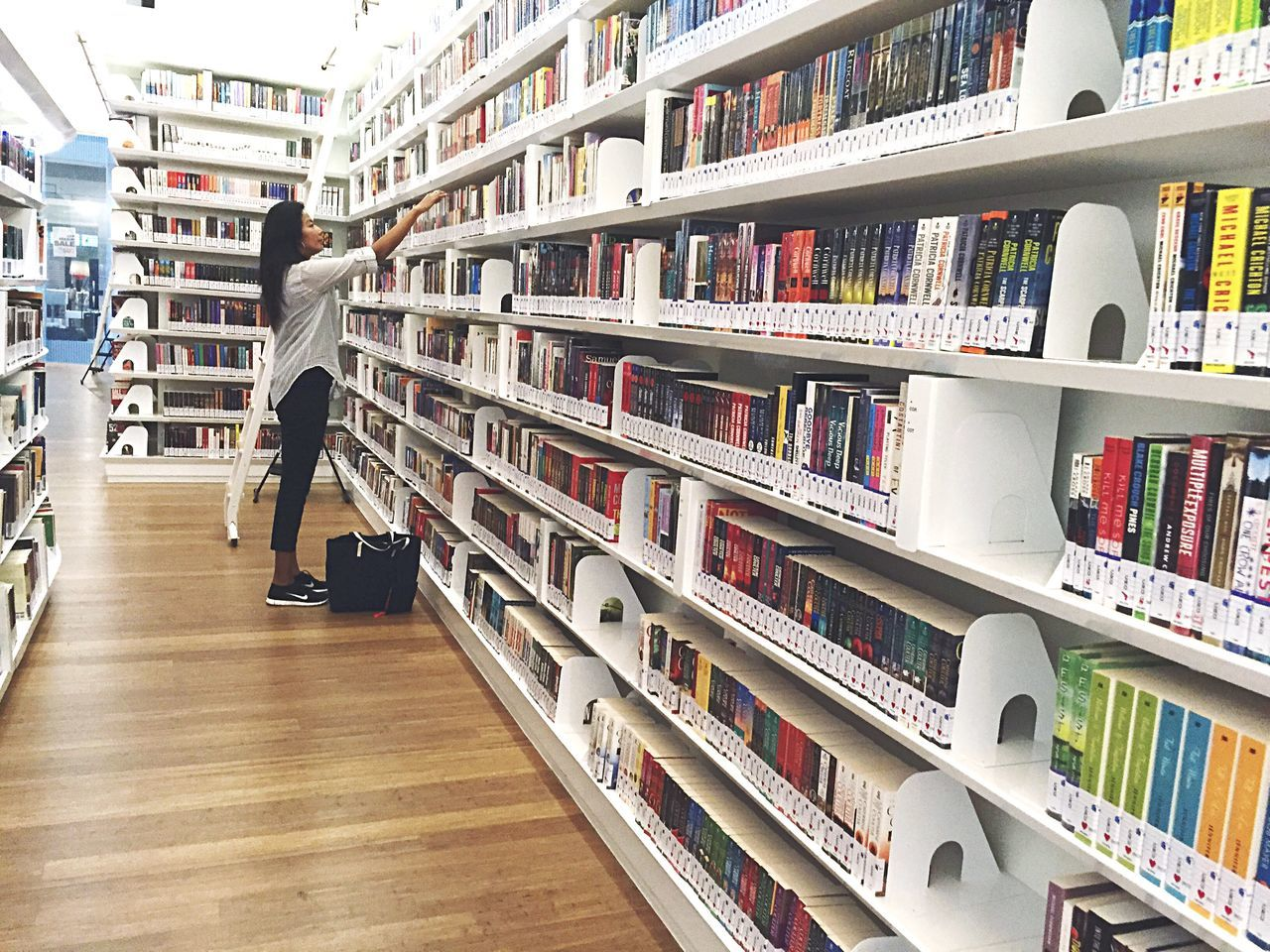 Woman Searching For Book In Library