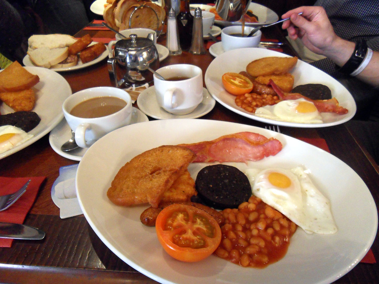 Bacon Beans Breakfast Coffee Eating Egg English Breakfast Food Food And Drink Freshness Hash Brown Human Body Part Human Hand Indoors  Plate Ready-to-eat Sausage Table Tea Toast Toasted Bread Tomato