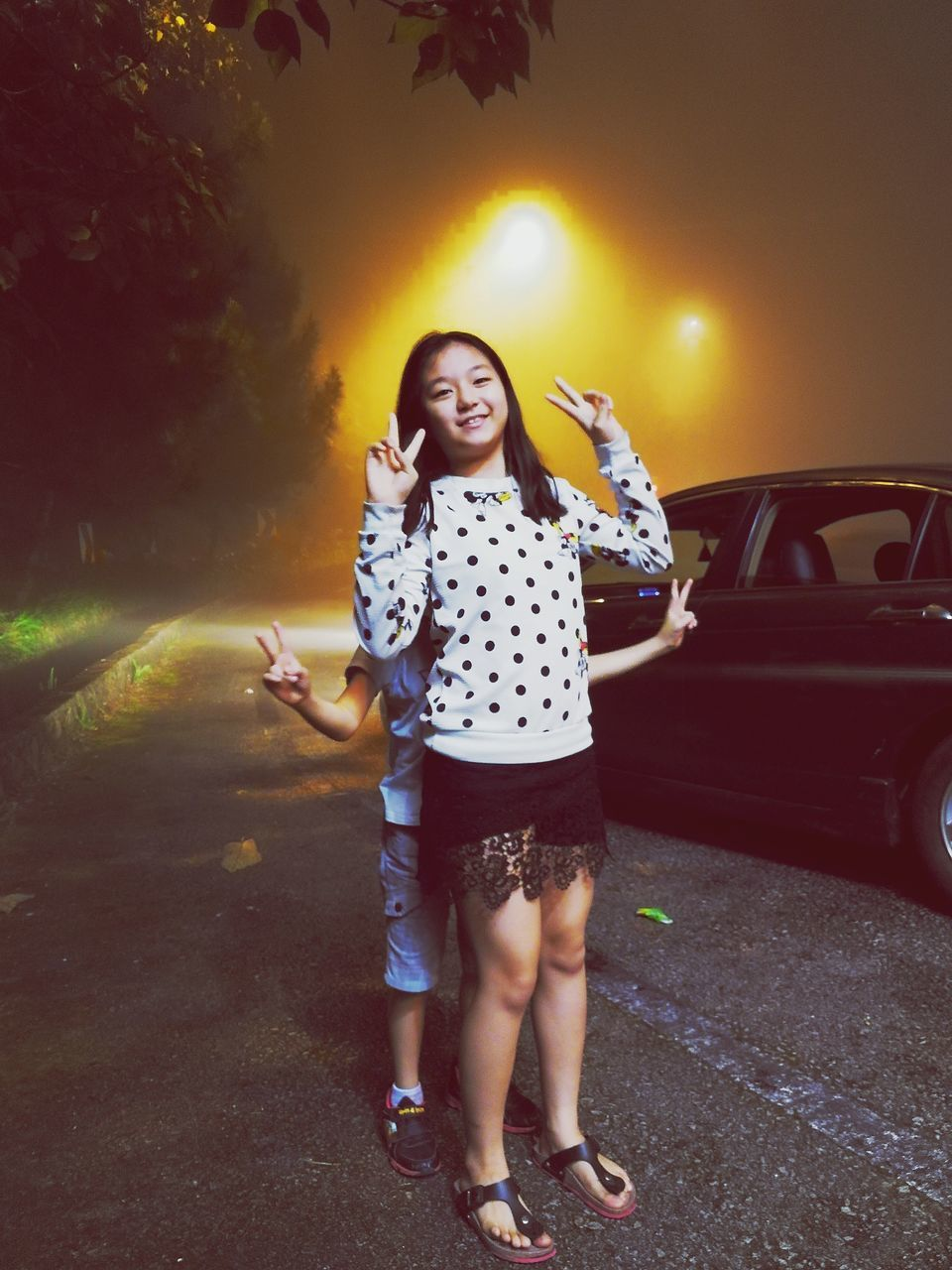 Sisters Showing Peace Sign While Standing By Car At Night