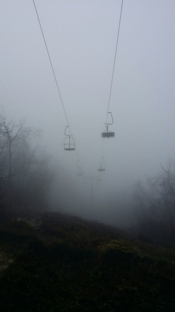 Low Angle View Of Overhead Cable Cars Against Sky During Foggy Weather