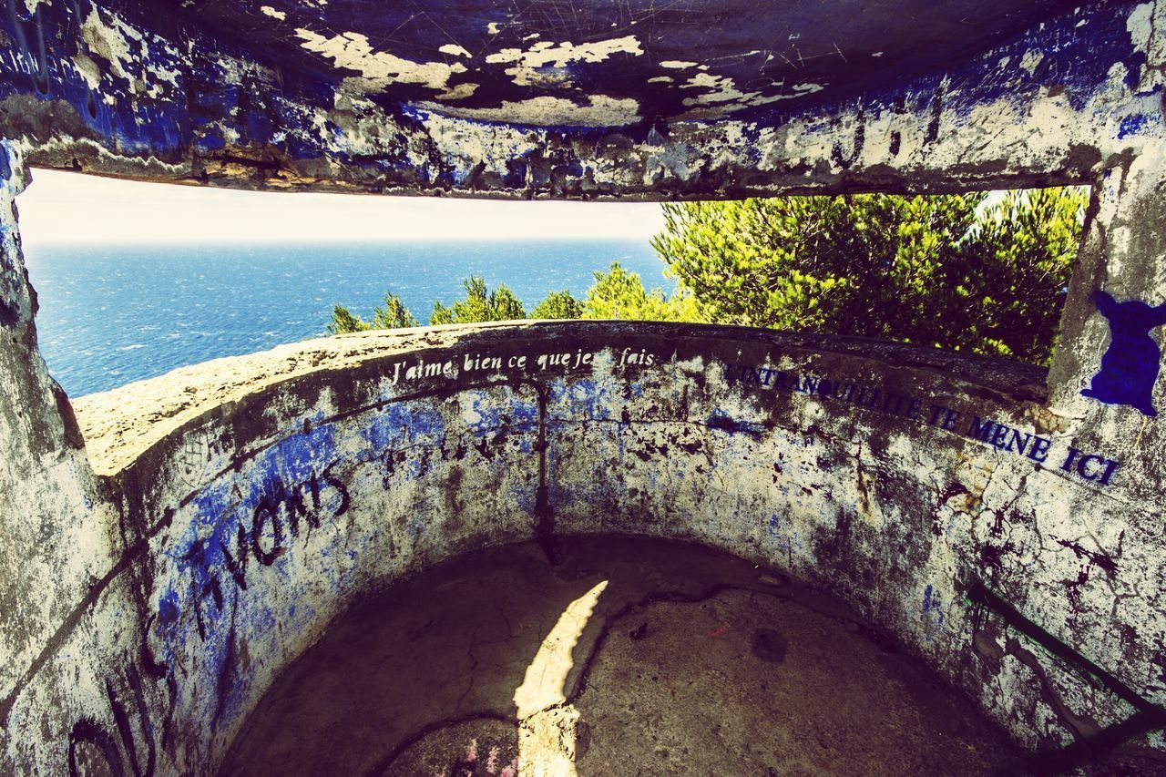 water, built structure, architecture, high angle view, day, old, rock - object, nature, arch, no people, outdoors, sea, wall - building feature, tranquility, tree, sunlight, sky, weathered, stone material, blue