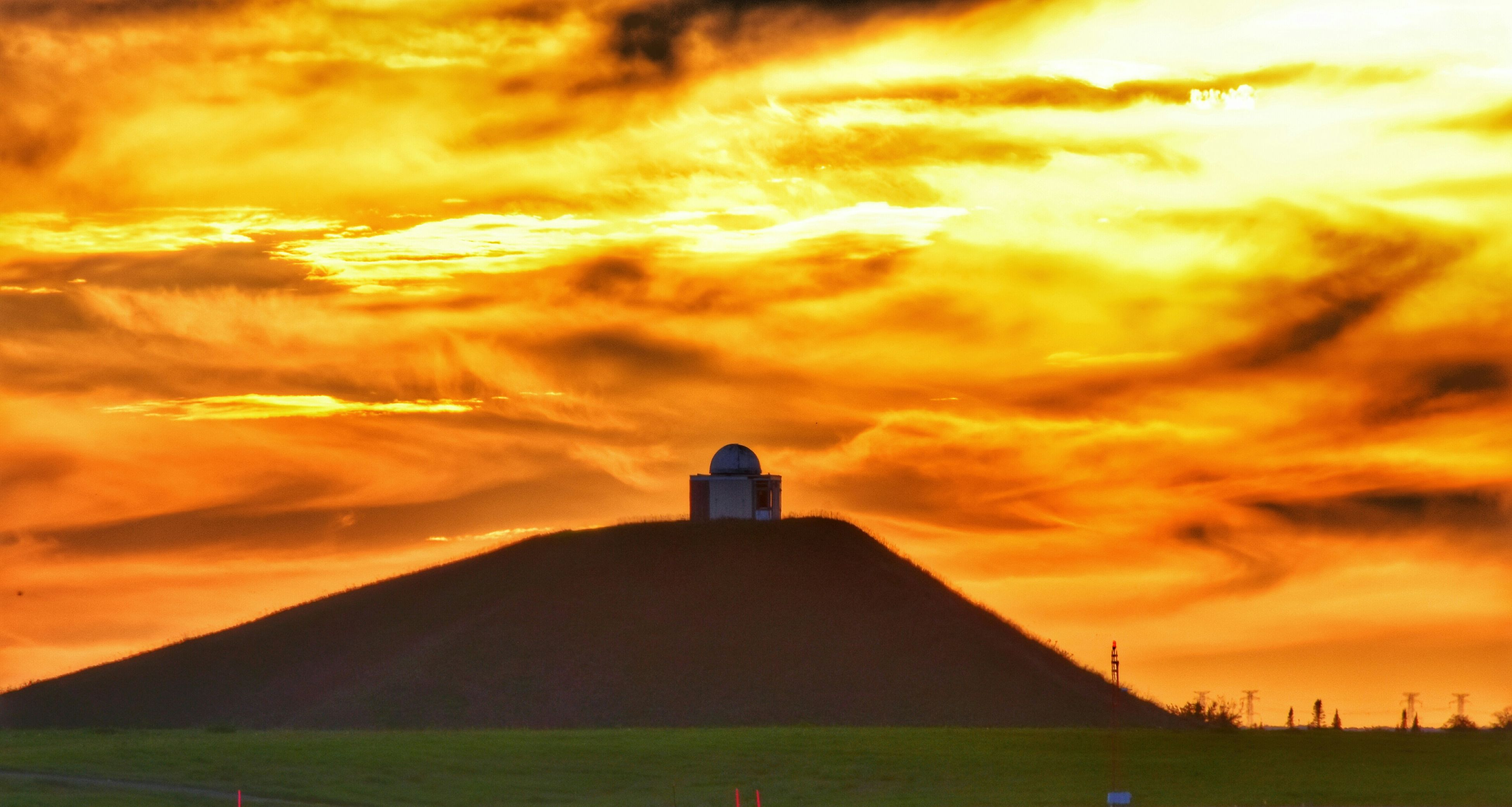 sunset, building exterior, architecture, built structure, sky, lighthouse, cloud - sky, orange color, cloudy, guidance, dramatic sky, tower, scenics, beauty in nature, silhouette, cloud, nature, weather, direction, tranquility