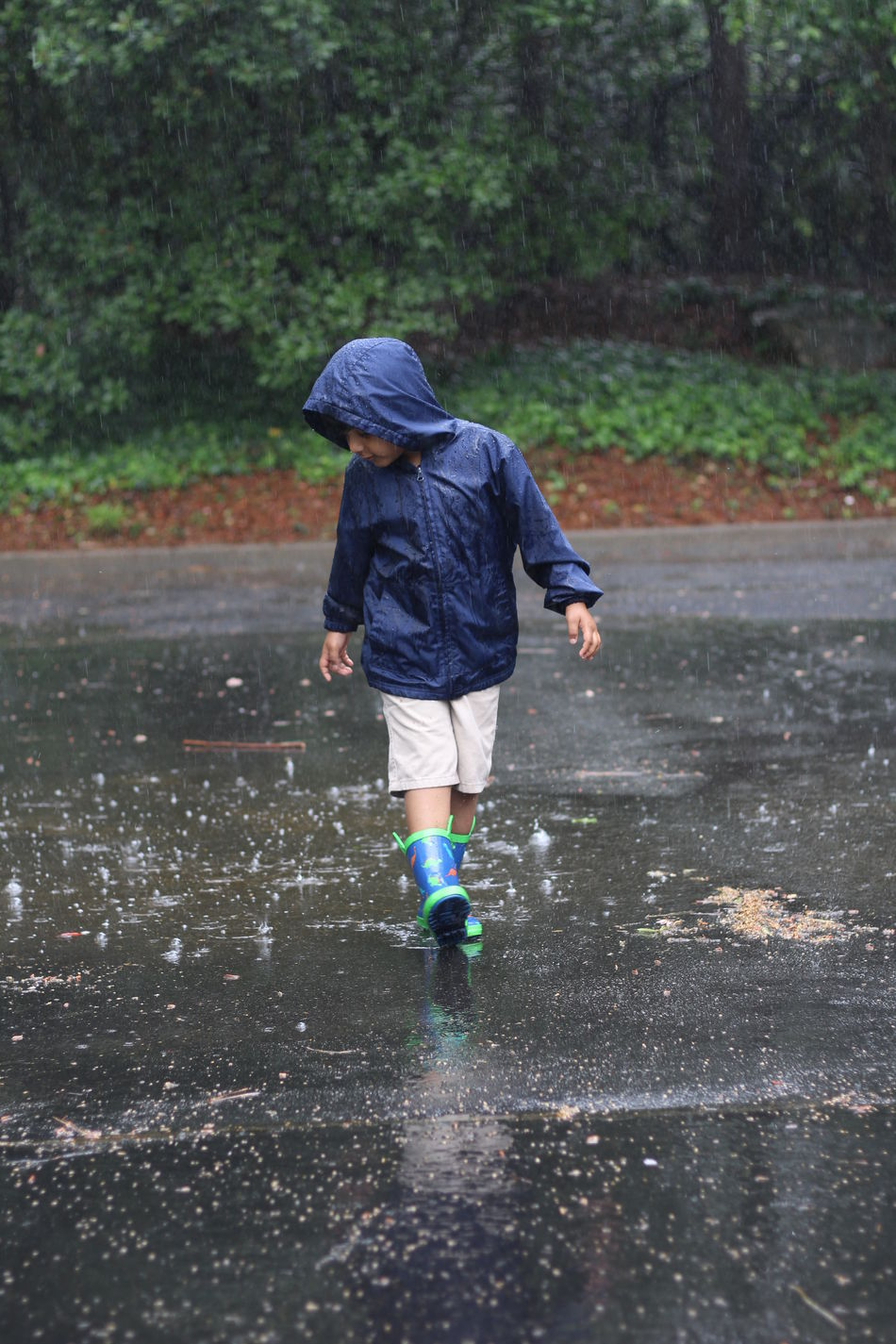 Casual Clothing Childhood Day Full Length Jumping Motion Nature One Person Outdoors People Rain Real People Rear View Tree Walking Warm Clothing Water Wet