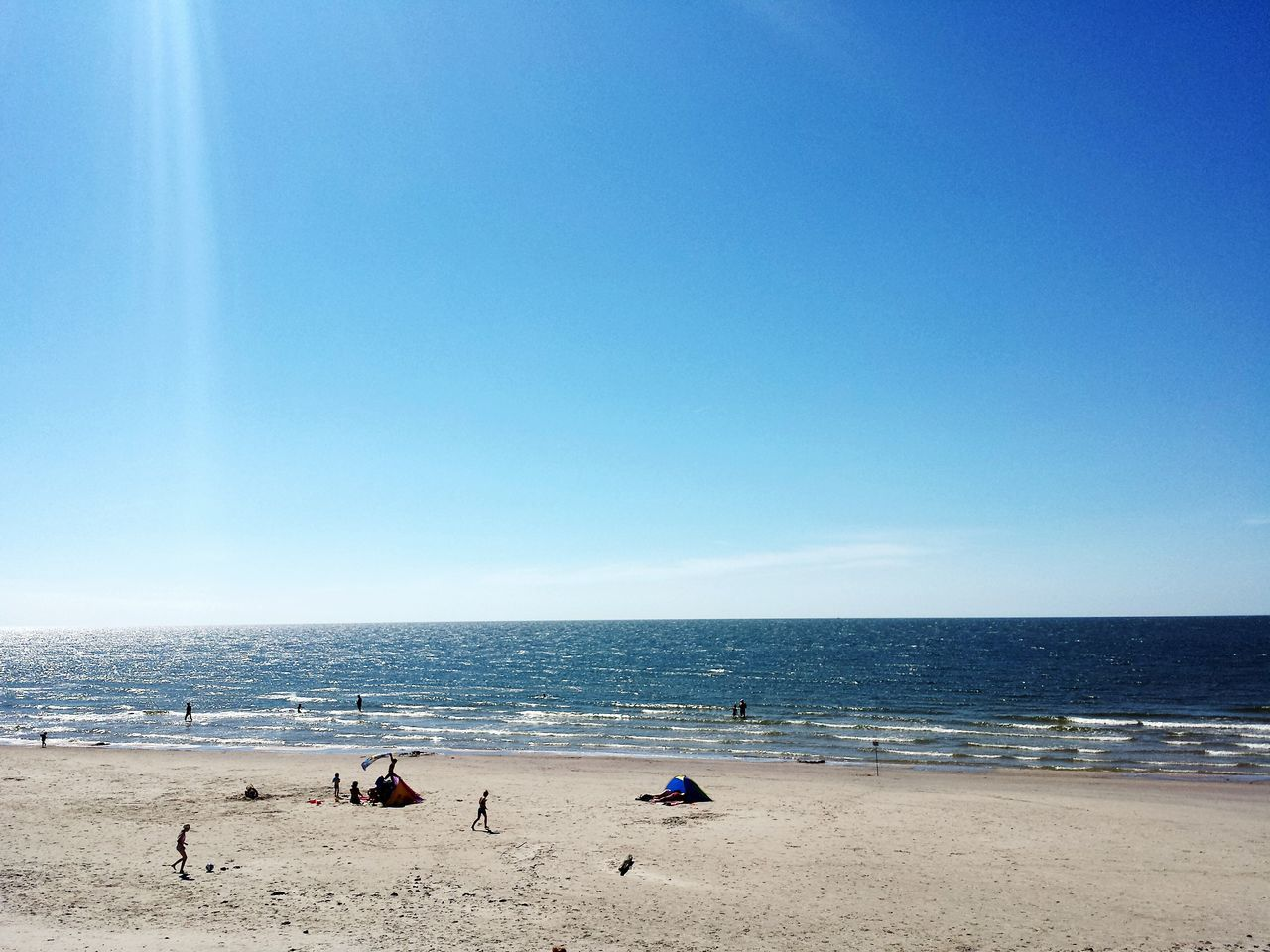 beach, sea, horizon over water, sand, copy space, blue, nature, clear sky, water, beauty in nature, real people, day, scenics, vacations, tranquil scene, tranquility, sunlight, outdoors, leisure activity, sky, summer, large group of people, lifestyles, men, people