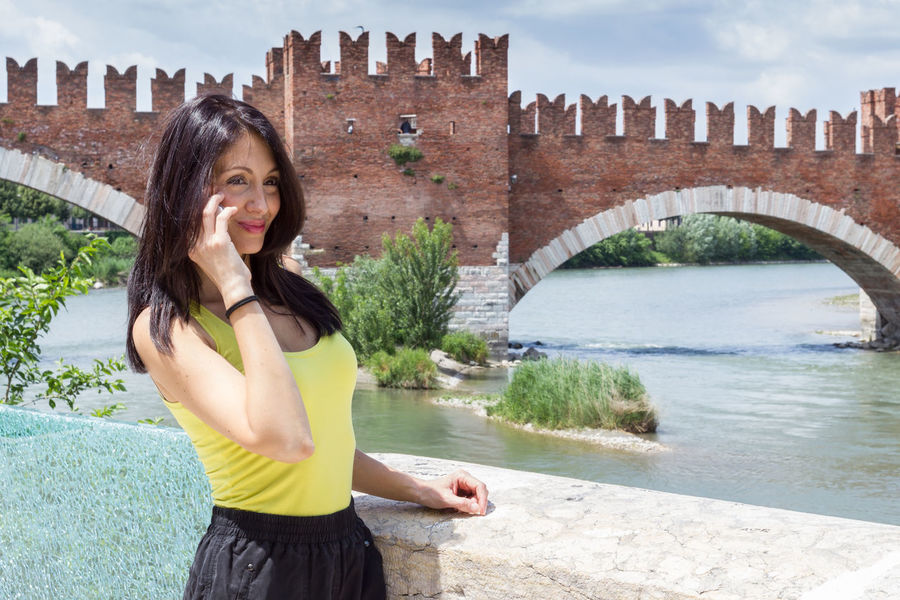 Portrait of a young woman talking on phone. In the background the medieval stone bridge Scaligero built in 14th century near Castelvecchio, Verona (Italy). Adige Ancient Architecture Attractive Background Bridge Brunette Call Castelvecchio Castle Cell Cheerful City Europe Female Fortress Girl Happy Historic Italian Italy Landmark Medieval Mobile Old