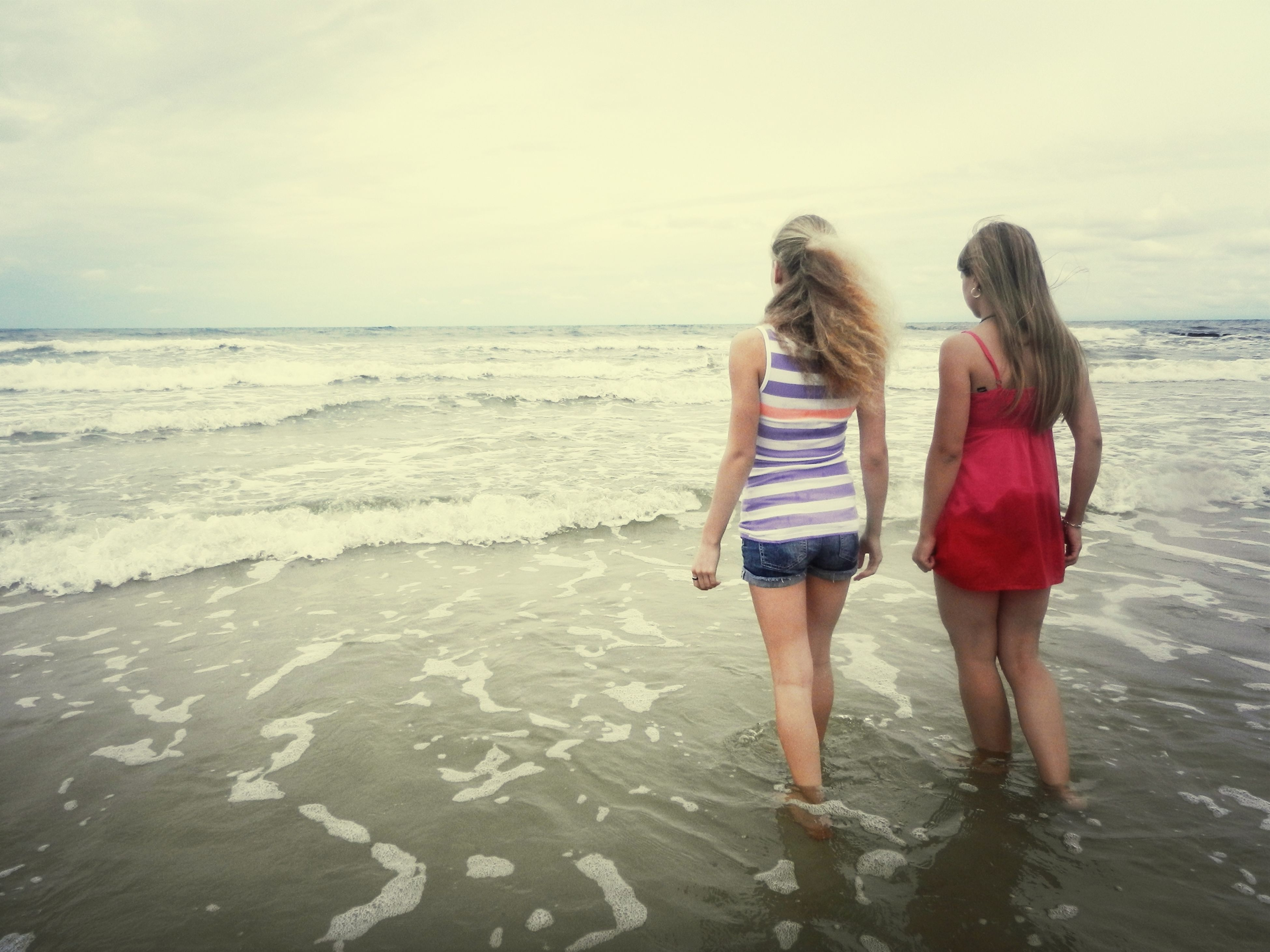 sea, beach, water, horizon over water, shore, lifestyles, leisure activity, rear view, full length, standing, vacations, sand, person, togetherness, sky, casual clothing, childhood, walking, girls