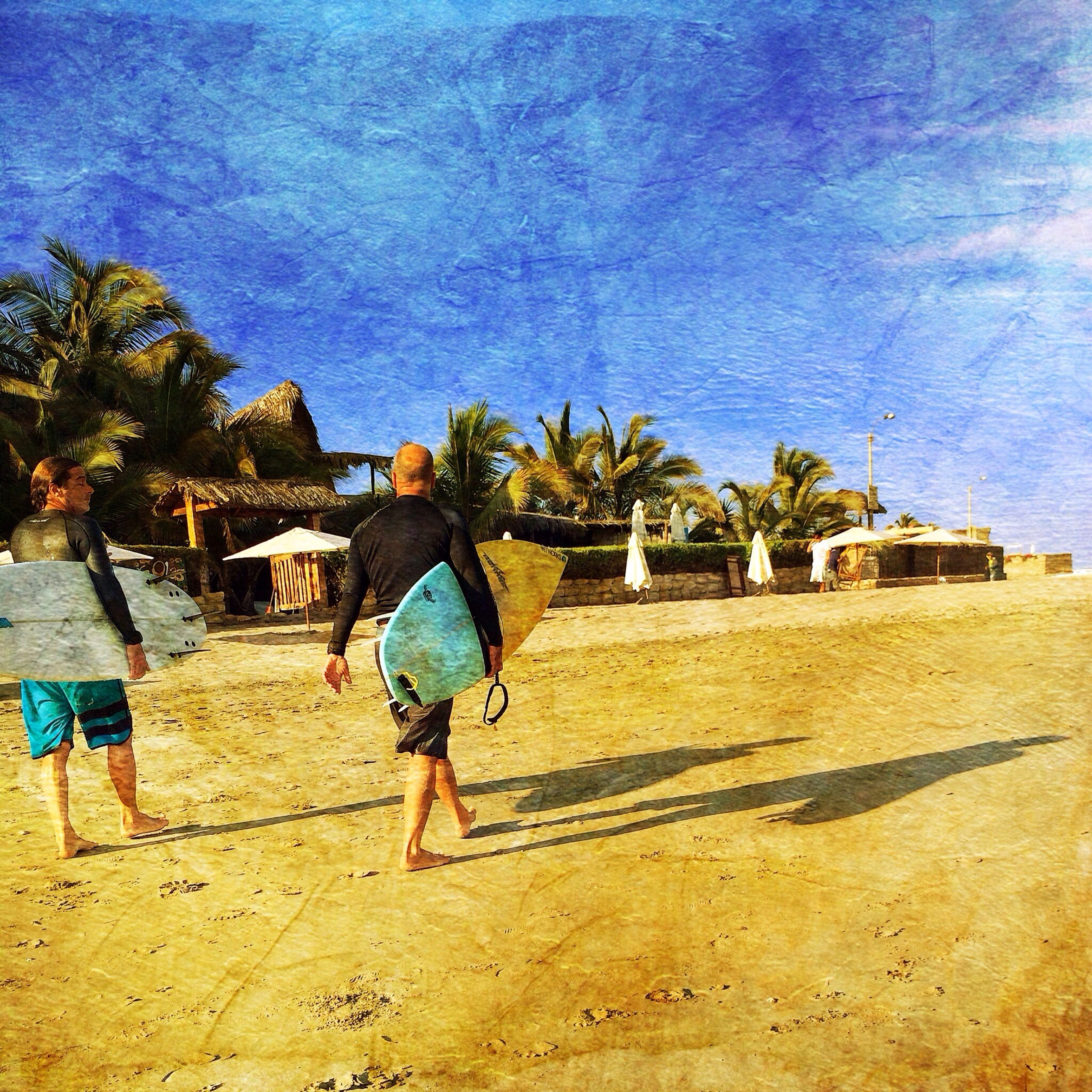 beach, sand, lifestyles, leisure activity, built structure, architecture, building exterior, blue, full length, tree, person, rear view, water, sky, men, sunlight, walking, shore