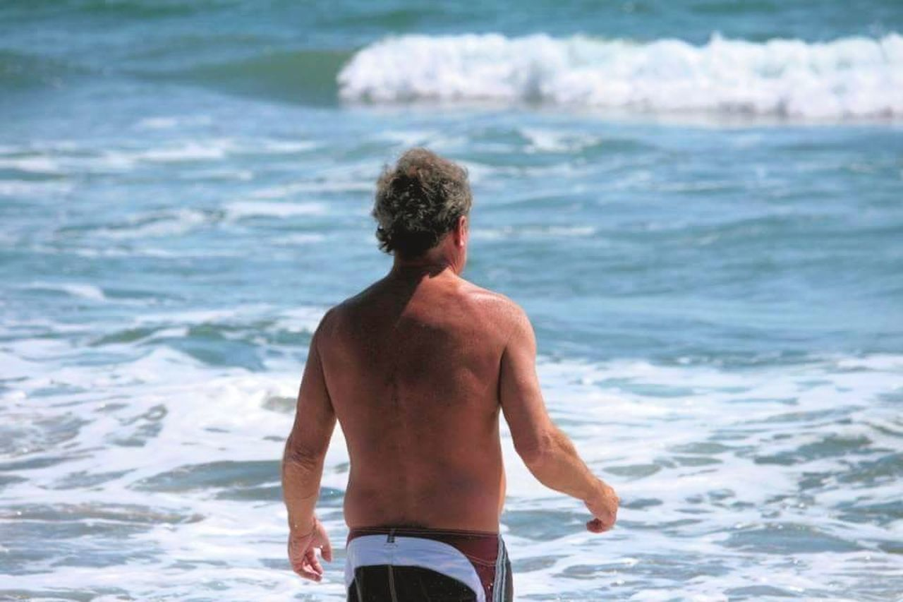 sea, shirtless, rear view, one person, wave, beach, standing, real people, men, water, day, leisure activity, lifestyles, vacations, ankle deep in water, outdoors, human back, one man only, nature, back, muscular build, beauty in nature, only men, adult, people, adults only