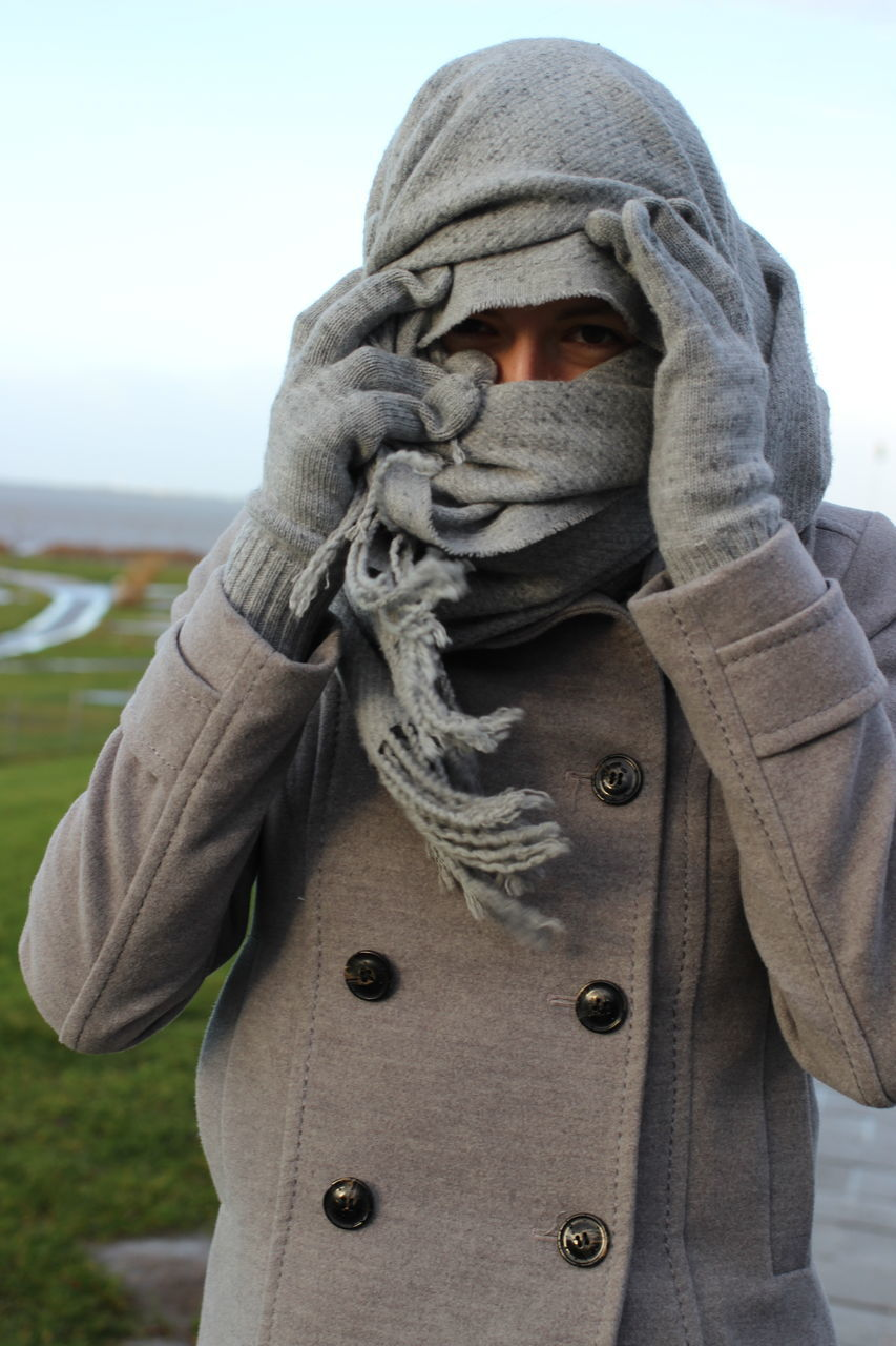 Woman Covering Face With Scarf During Winter