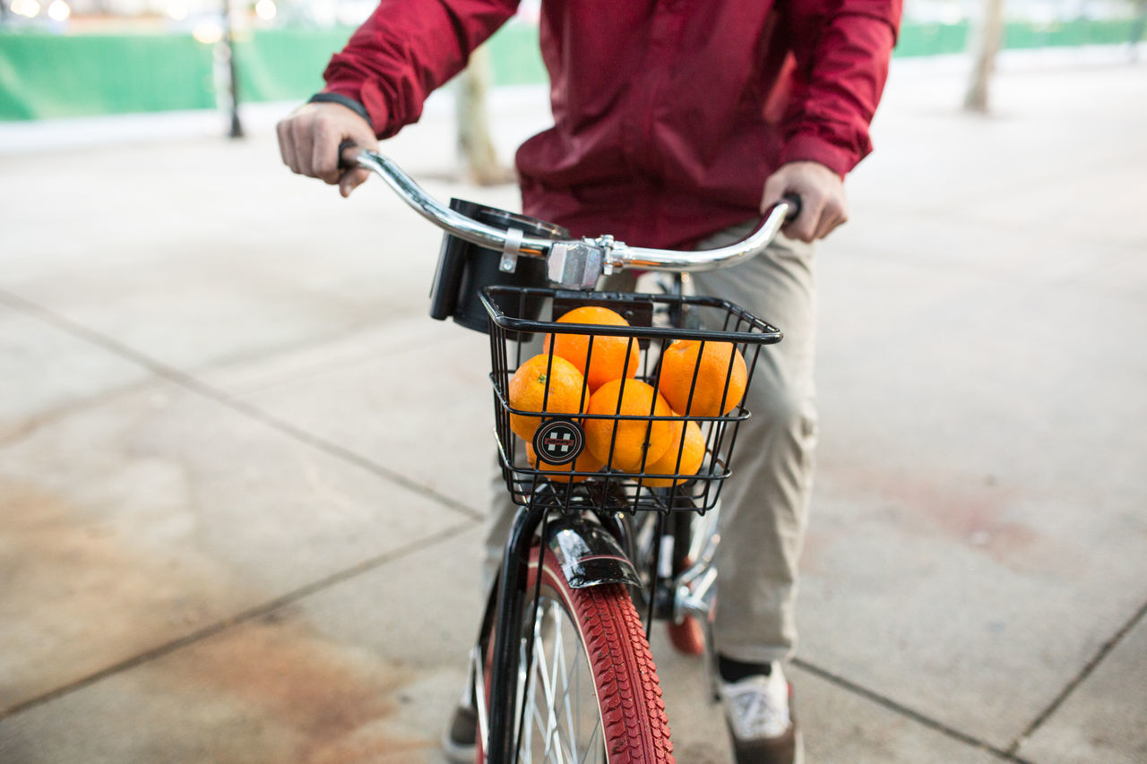 Midsection Of Man Cycling With Fresh Oranges In Basket