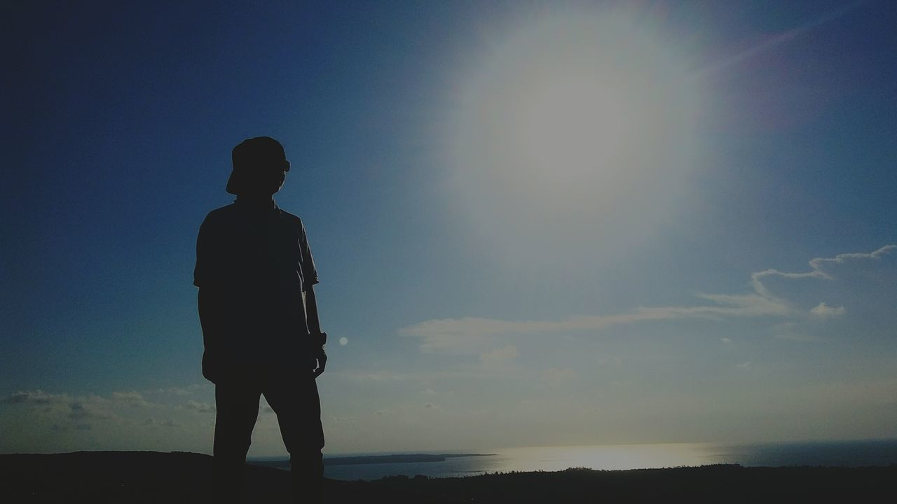 standing, sky, one person, real people, silhouette, sea, rear view, nature, full length, sunlight, outdoors, sun, men, leisure activity, tranquil scene, water, tranquility, beauty in nature, sunset, horizon over water, lifestyles, beach, scenics, day, clear sky, people