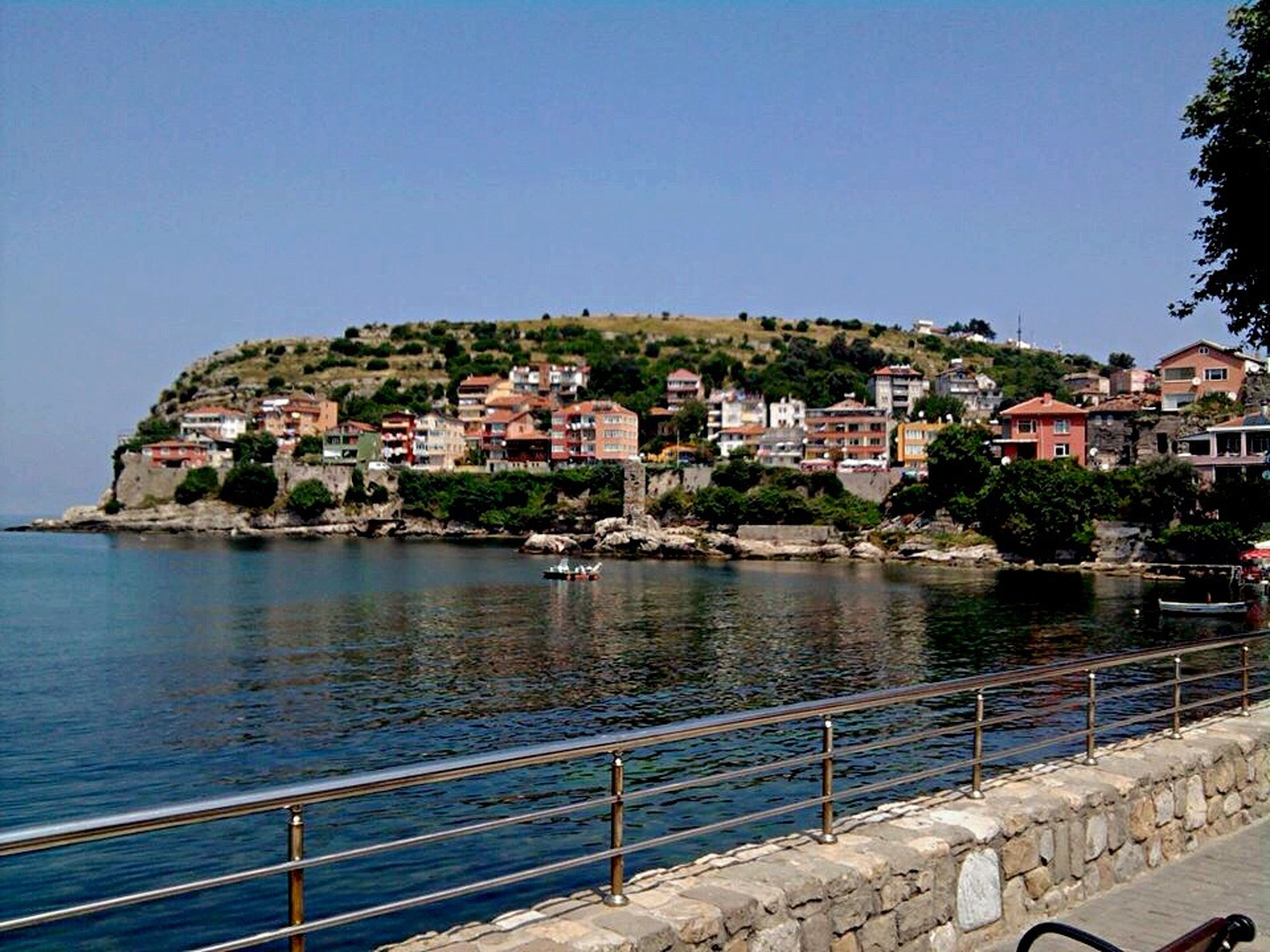architecture, building exterior, house, built structure, residential building, clear sky, water, town, outdoors, no people, blue, travel destinations, day, sea, mountain, city, nautical vessel, sky, community, cityscape, nature, tree