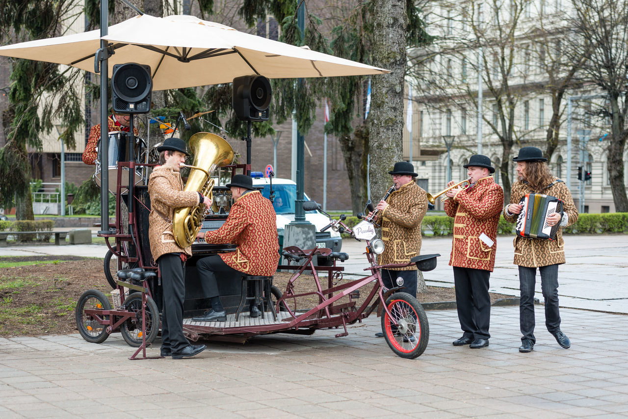 transportation, real people, mode of transport, full length, day, outdoors, men, land vehicle, lifestyles, leisure activity, bicycle, tree, women, large group of people, young adult, warm clothing, adult, people