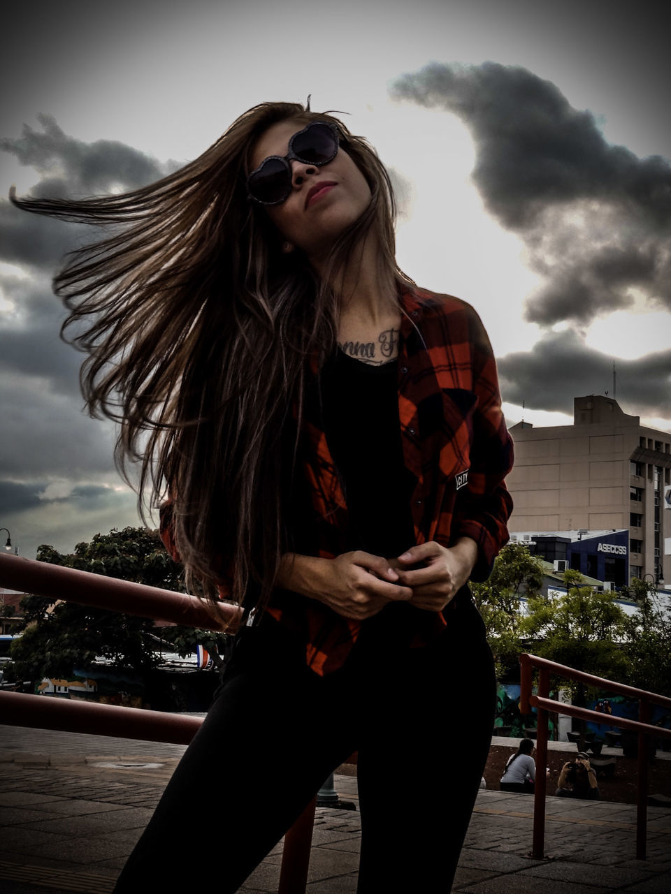 Young Woman With Tousled Hair Standing By Railing Against Cloudy Sky