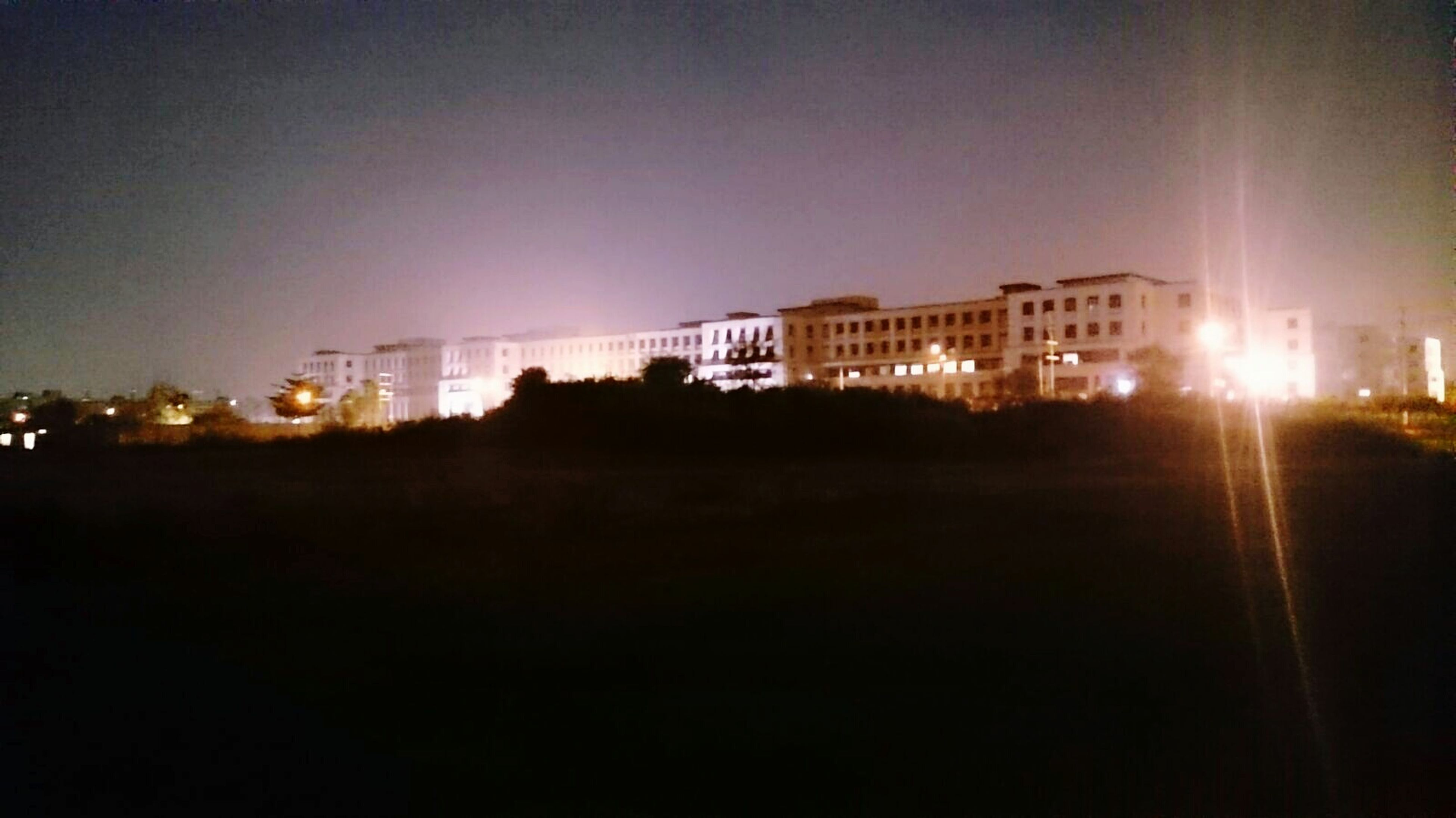 illuminated, night, architecture, built structure, city, dark, building, residential building, cityscape, sky, no people, outdoors, city life, residential district, glowing, light, nature, growth
