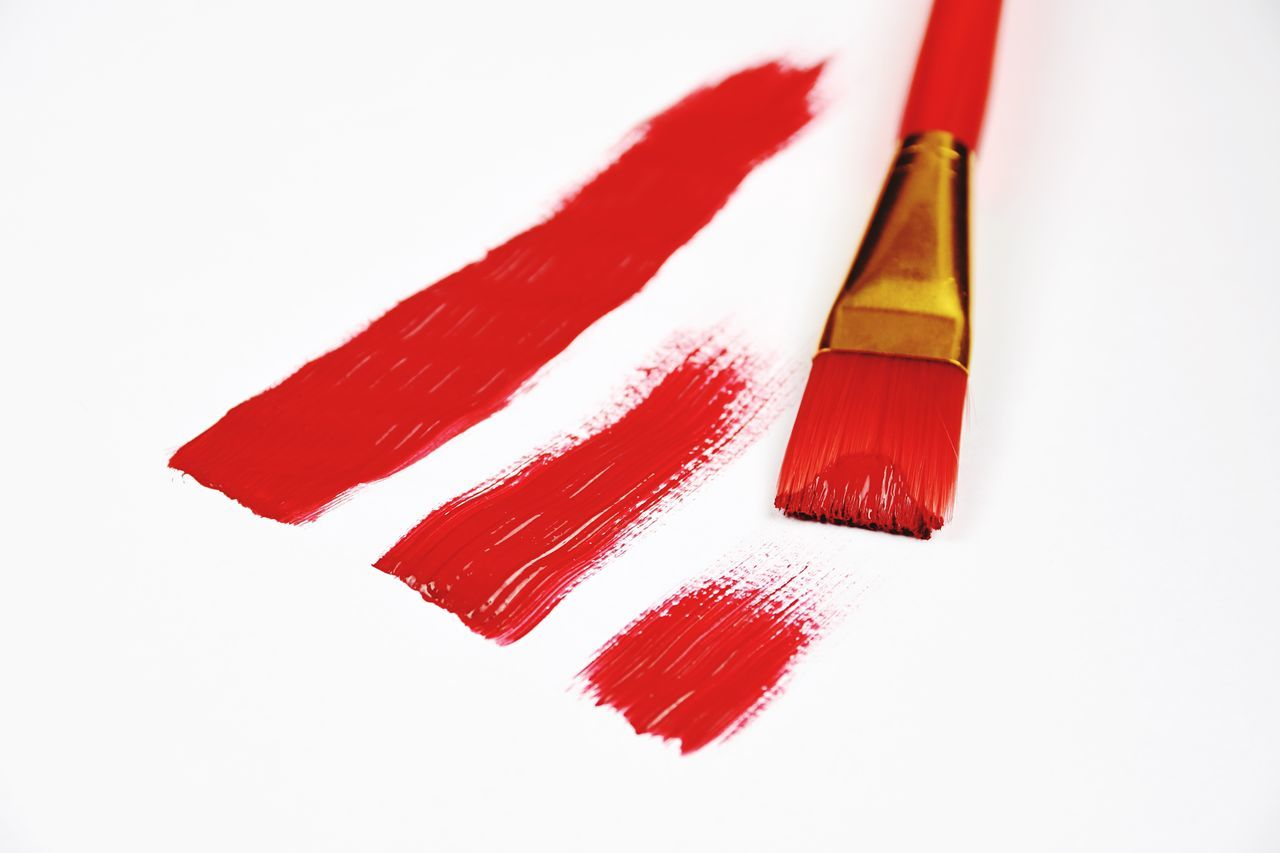 High Angle View Of Brush And Red Paint On White Background