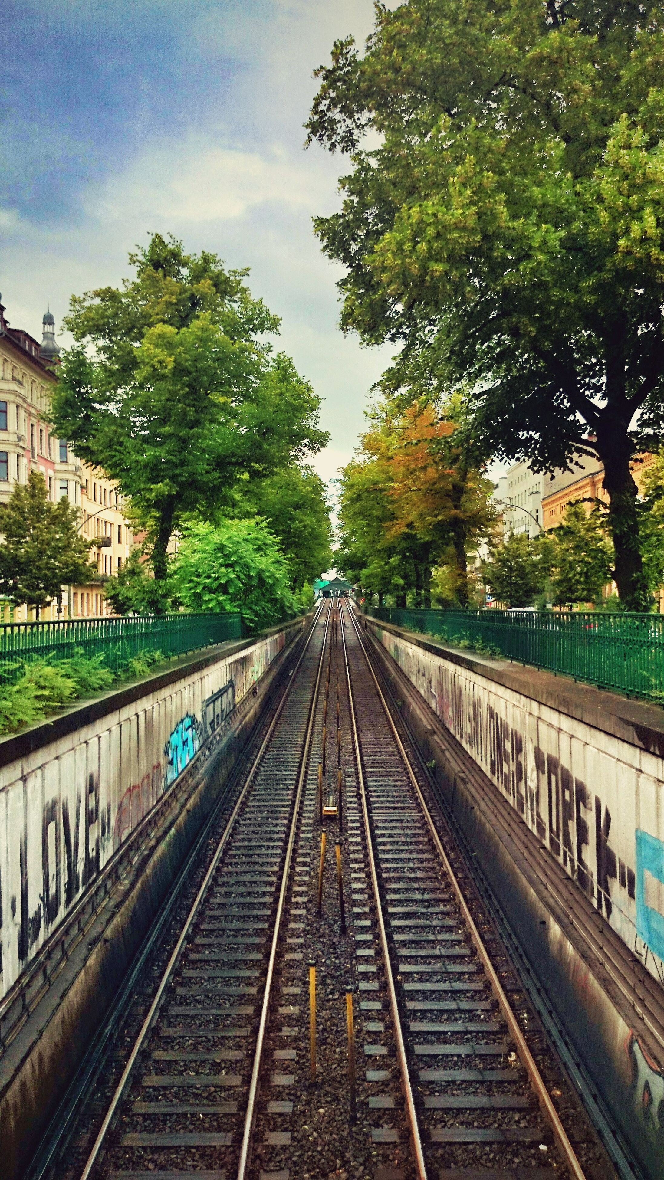 railroad track, rail transportation, transportation, tree, diminishing perspective, the way forward, built structure, architecture, vanishing point, public transportation, sky, railing, building exterior, railway track, railroad station platform, day, high angle view, railroad station, city, connection