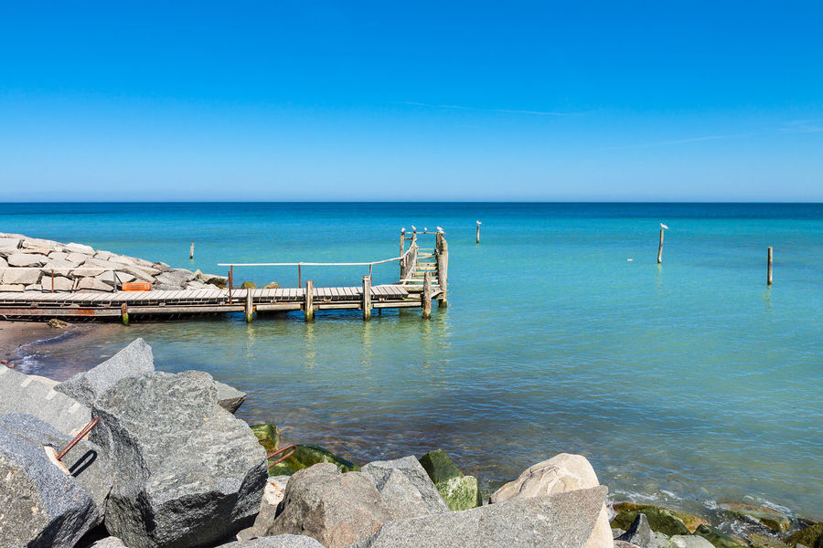 Baltic Sea coast on the island Ruegen, Germany. Baltic Sea Beach Beauty In Nature Blue Clear Sky Coast Day Horizon Over Water Landing Stage Landscape Nature No People Outdoors Rocks Ruegen Sea Shore Sky Stones Tourism Travel Destinations Vacations Vitte Water