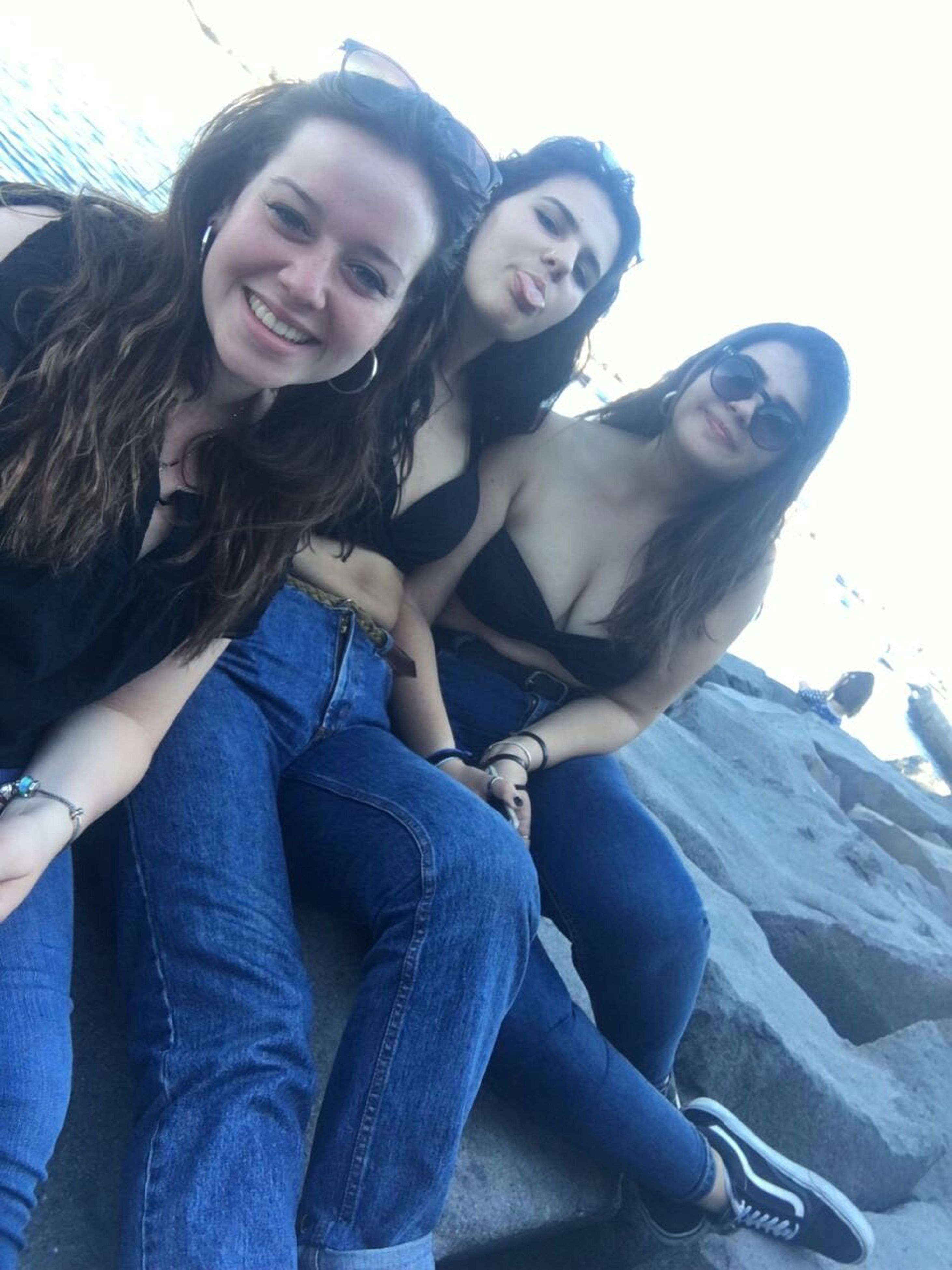 smiling, young women, looking at camera, casual clothing, young adult, happiness, portrait, togetherness, leisure activity, front view, real people, sitting, day, outdoors, lifestyles, two people, friendship, beautiful woman, posing, nature, beauty in nature