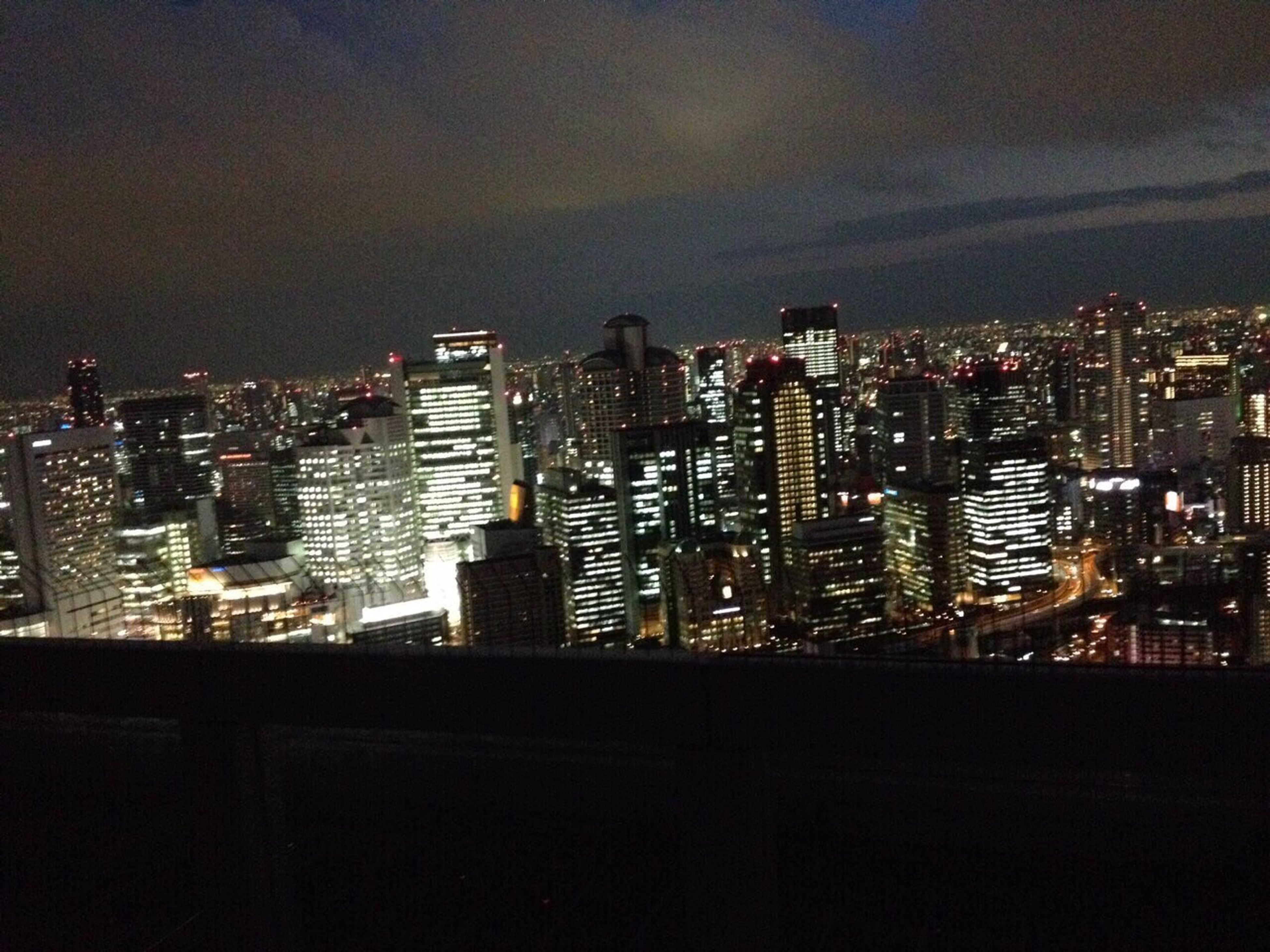 illuminated, building exterior, cityscape, city, night, architecture, built structure, skyscraper, modern, crowded, residential building, sky, high angle view, office building, dark, tower, residential district, city life, residential structure, urban skyline