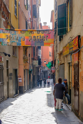 Genoa, Italy Architecture Building Exterior Built Structure City City Life Commercial Sign Day Footpath Full Length Leisure Activity Lifestyles Men Narrow Outdoors Person Rear View Residential Building Residential Structure Street The Way Forward Walking