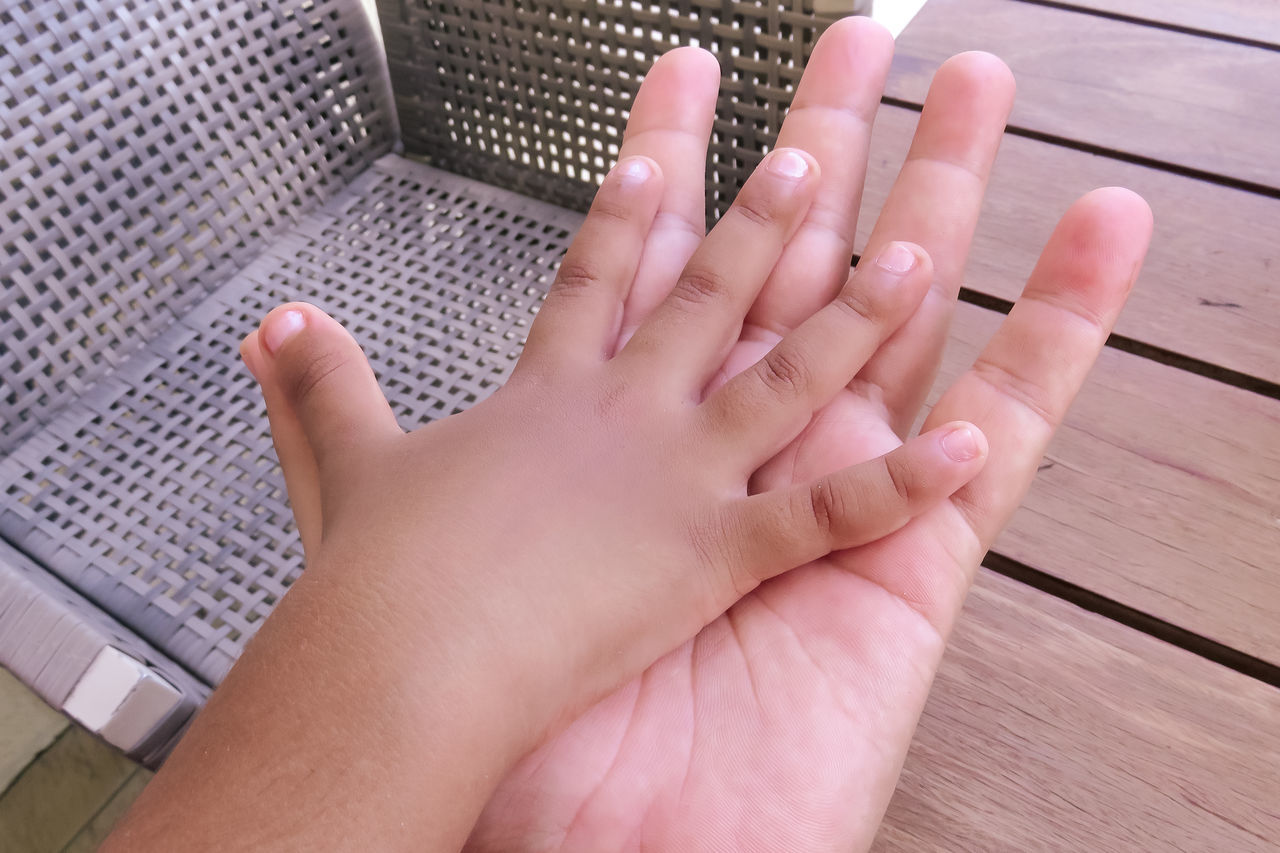 Close-Up Of Child's And Adult's Hands