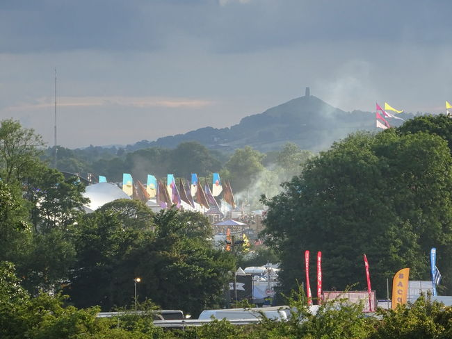 Beauty In Nature Festival Season Flags Glastonbury 2014 Glastonbury Tor Hazy Sky Hill Landscape Multi Colored Nature Outdoors Tranquil Scene