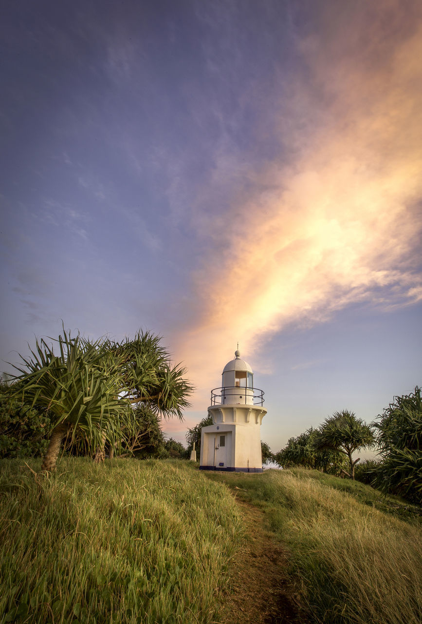 architecture, building exterior, built structure, sky, grass, cloud - sky, sunset, nature, growth, no people, spirituality, beauty in nature, lighthouse, outdoors, field, tree, tranquility, place of worship, scenics, day