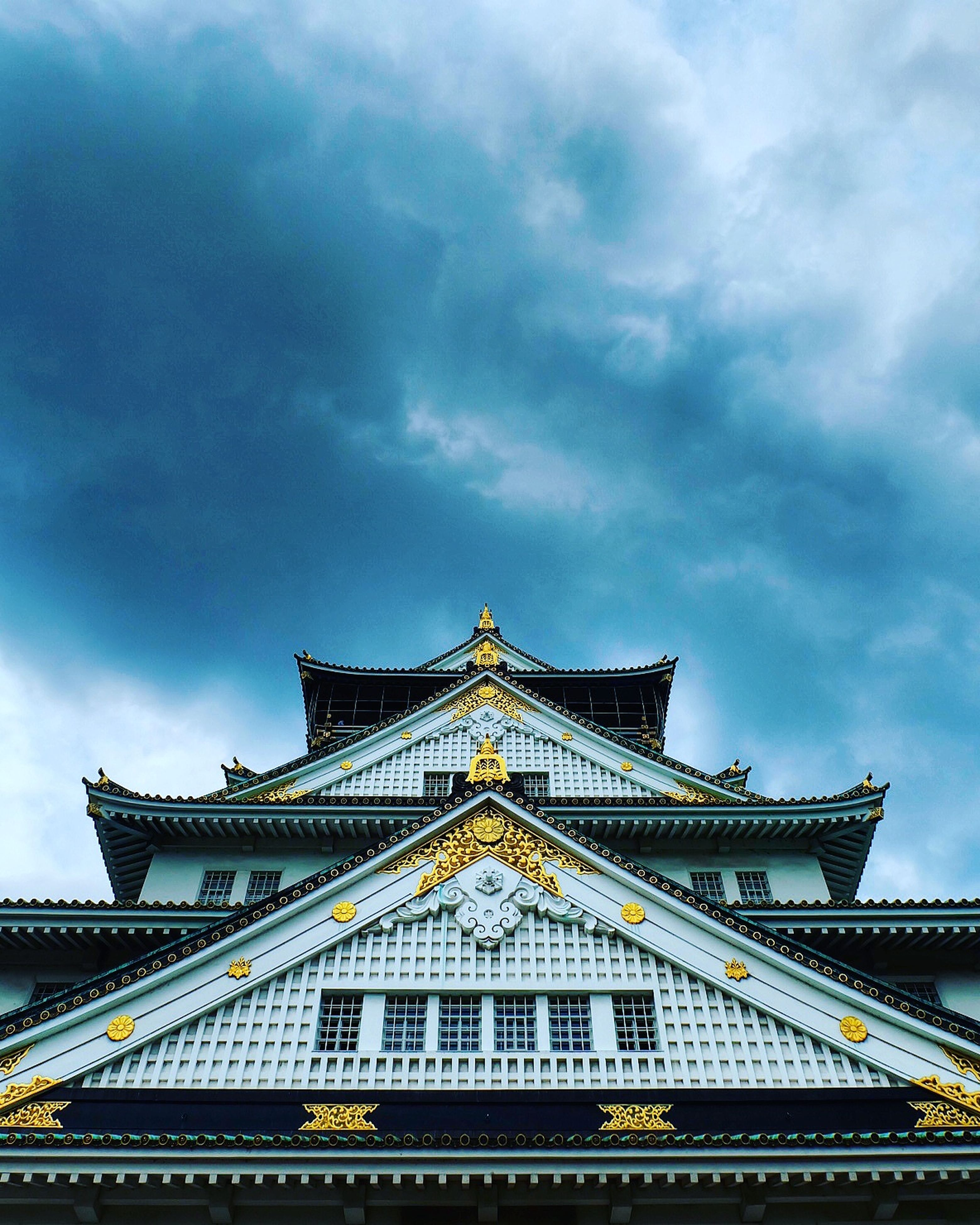 architecture, built structure, building exterior, low angle view, travel destinations, sky, high section, tourism, architectural feature, famous place, roof, pagoda, place of worship, cloud - sky, temple - building, blue, cloudy, outdoors, culture, arch, history, gothic style, traditional