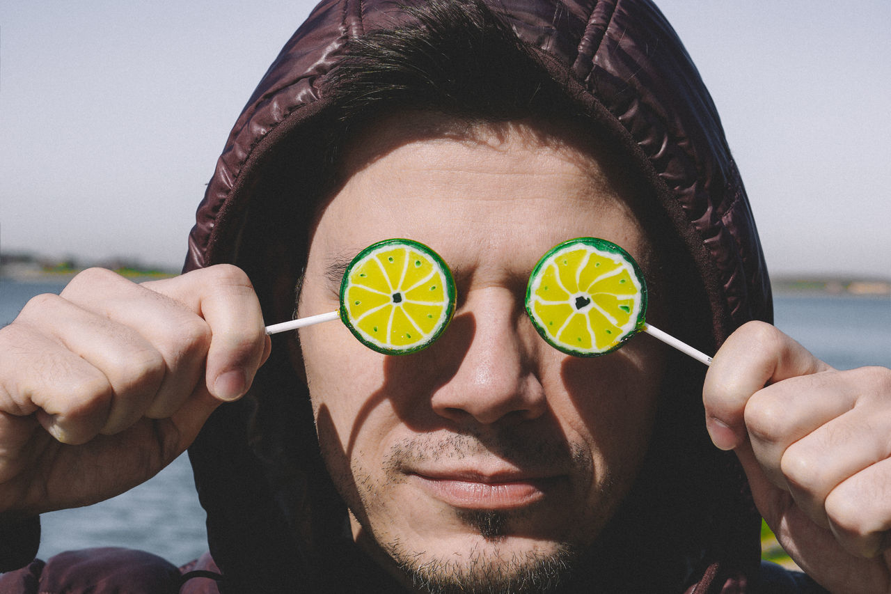 Lemon Eyes Eyes Front View One Person Adults Only Headshot Human Body Part One Man Only People Holding Close-up Adult Portrait Human Hand Day Outdoors Lollipop Warm Clothing Sunny Day Resist EyeEm Diversity TCPM The Portraitist - 2017 EyeEm Awards Place Of Heart