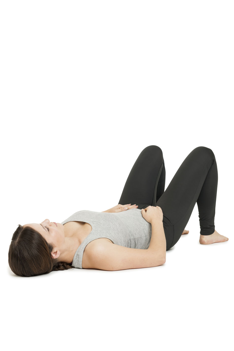 """Flat angular full body view of a lying on the back young woman in yoga position """"happy baby"""" (anada balasana) on a white background. Anada Balasana Añada Balasana Beautiful Woman Breath Day Happy Baby Indoors  Lifestyles Lying Down Lying On Back Meditation One Person Relaxation Resting Studio Shot White Background Women Yoga Yoga Position Of The Child Young Adult Young Women"""