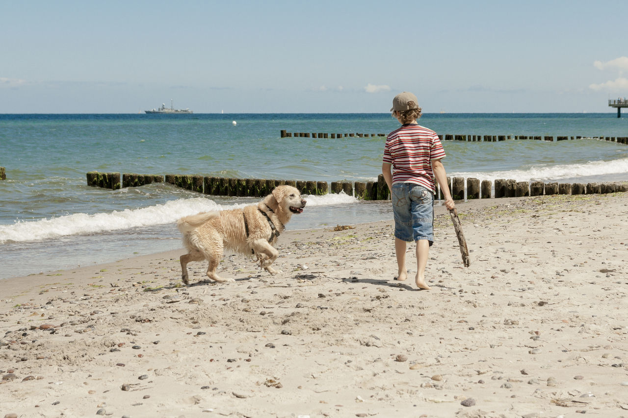 Boy with his dog Animal Animal Themes Baltic Sea Beach Casual Clothing Day Dog Domestic Animals Golden Retriever Horizon Over Water Leisure Activity Life For The Story Mammal Nature One Animal One Person Outdoors Pet Leash Pets Rear View Sand Sea Sky Live For The Story