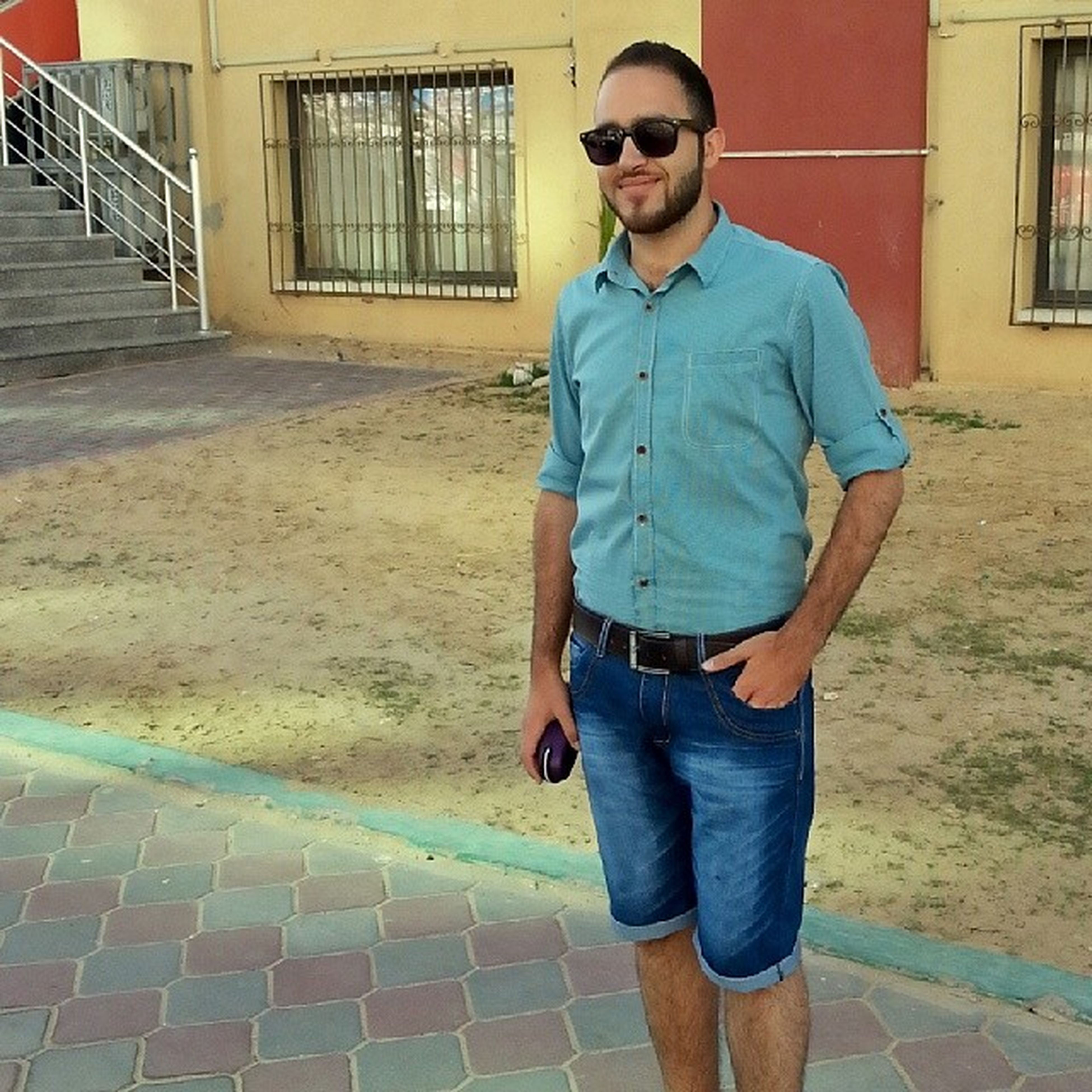 casual clothing, person, building exterior, architecture, built structure, front view, young adult, looking at camera, portrait, lifestyles, standing, young men, full length, leisure activity, sunglasses, jacket, three quarter length, hands in pockets