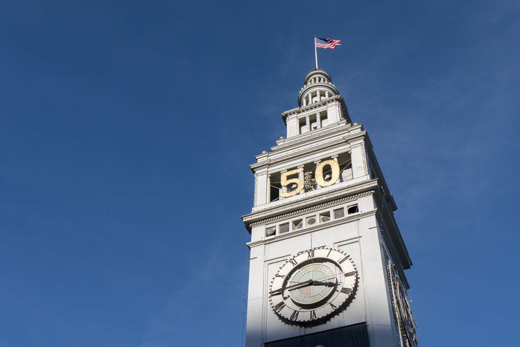 Architecture Blue Building Exterior Built Structure Clear Sky Clock Clock Tower Copy Space Day Famous Place Flag High Section Low Angle View Outdoors Patriotism Sky Super Bowl Tall - High Time Tower Travel Destinations