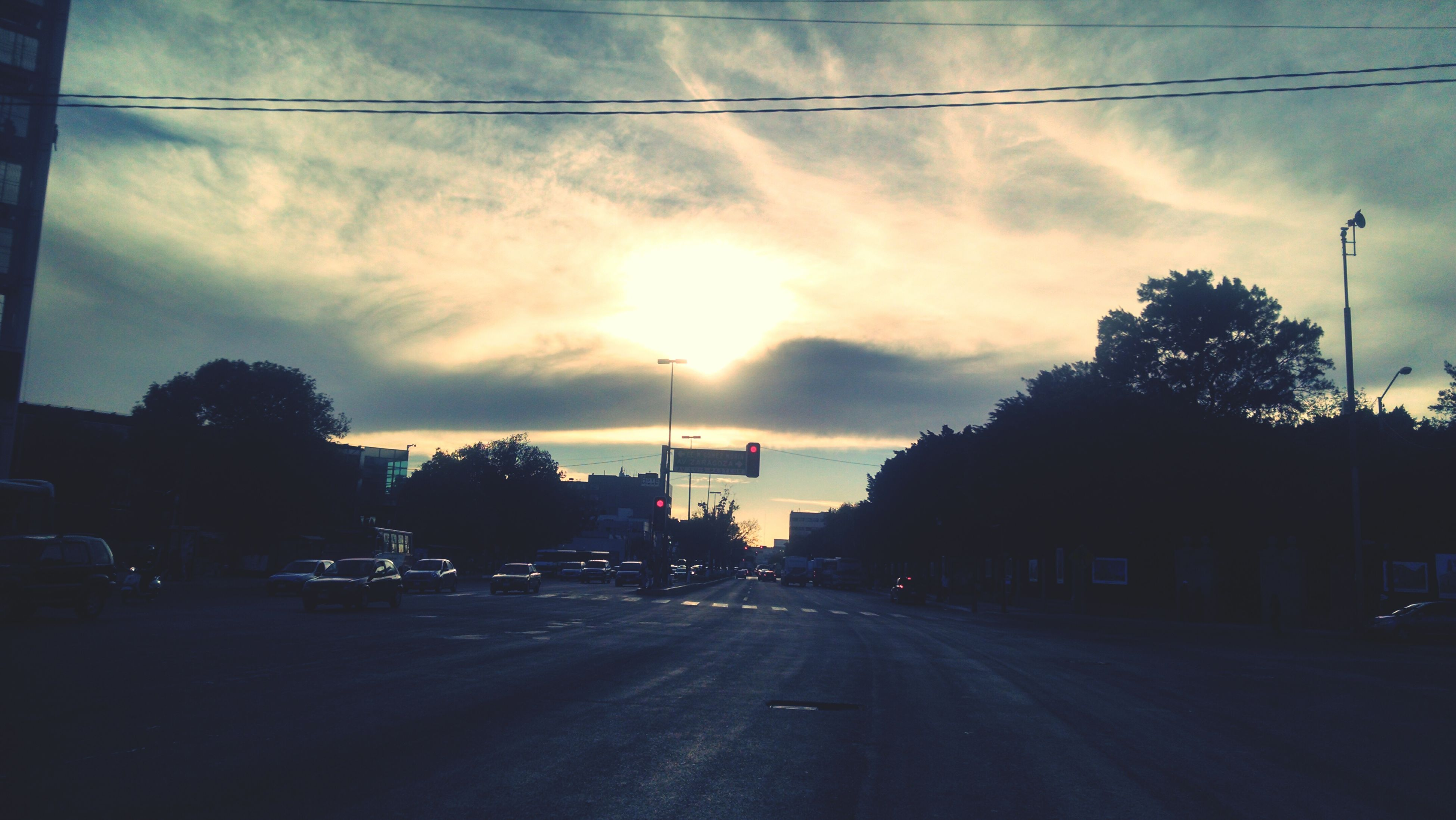 sunset, sky, road, transportation, cloud - sky, silhouette, street, the way forward, tree, street light, car, cloud, cloudy, power line, electricity pylon, land vehicle, sun, diminishing perspective, road marking, sunlight