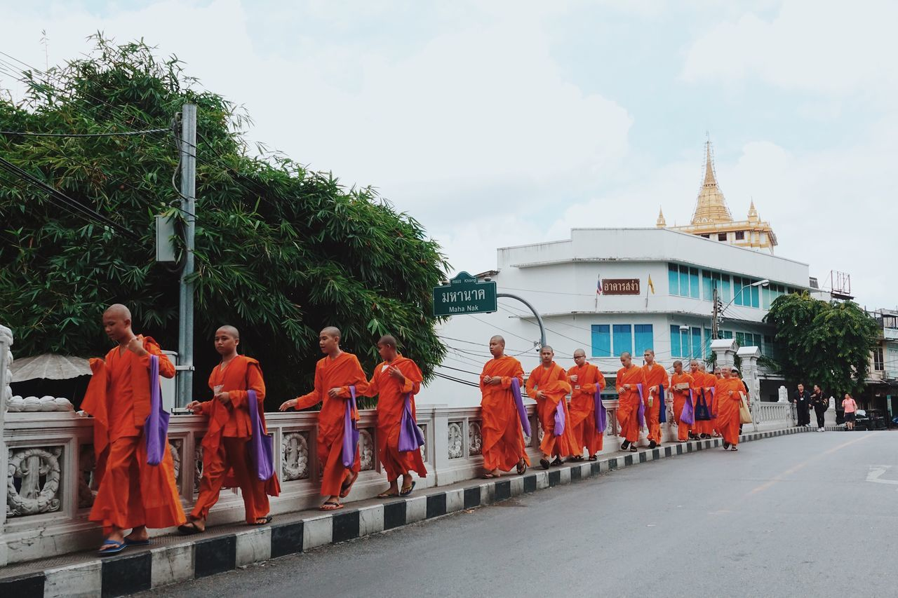 Real People Sky Men Religion Day Built Structure Architecture Cloud - Sky Large Group Of People Tree Outdoors Building Exterior Adult Adults Only People Monk  Buddhism Orange Color Streetphotography Street Bangkok Thailand. Walking Walking In Line Street Photography Cultures