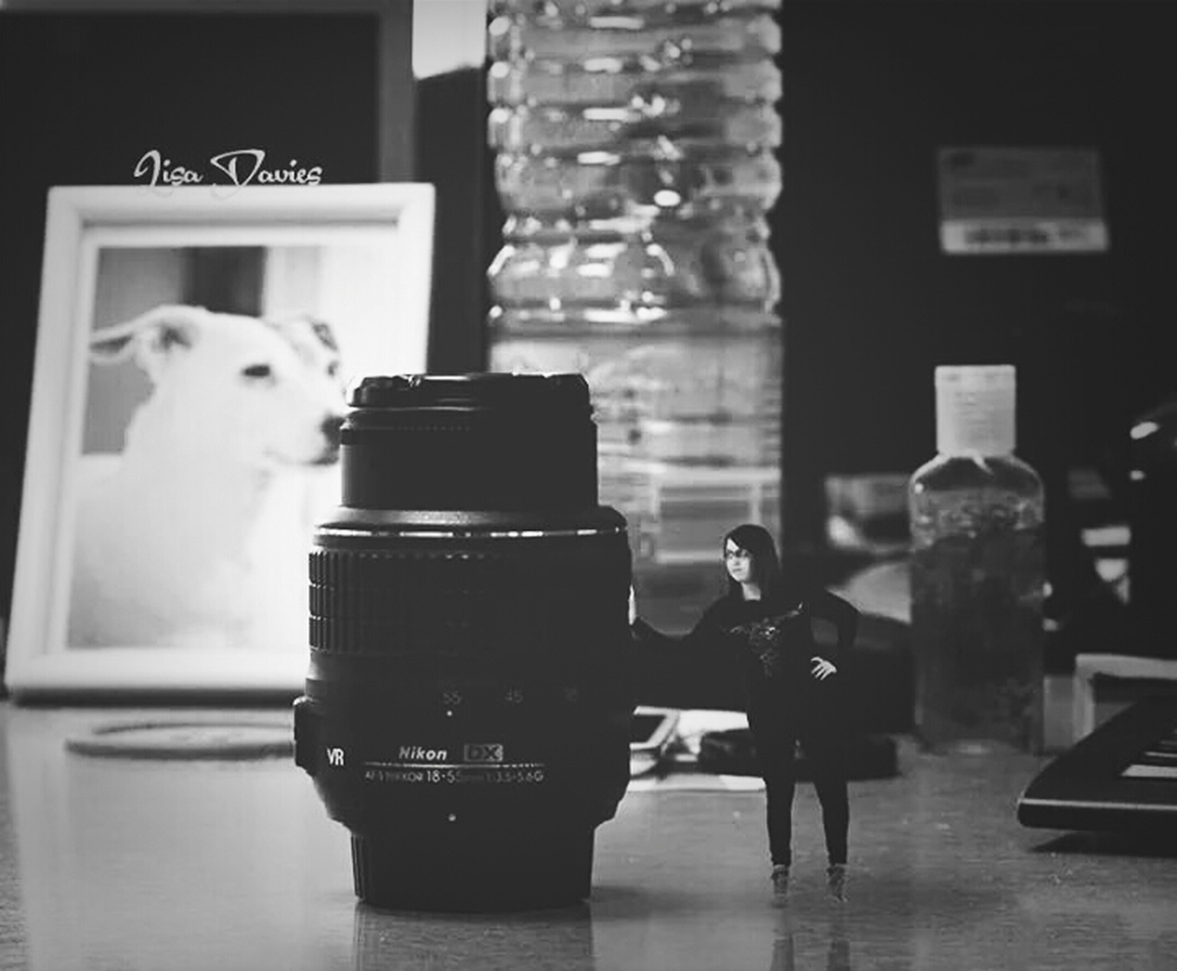 indoors, table, communication, close-up, reflection, focus on foreground, still life, text, drink, western script, technology, photography themes, selective focus, food and drink, no people, camera - photographic equipment, refreshment, home interior, bottle, glass - material