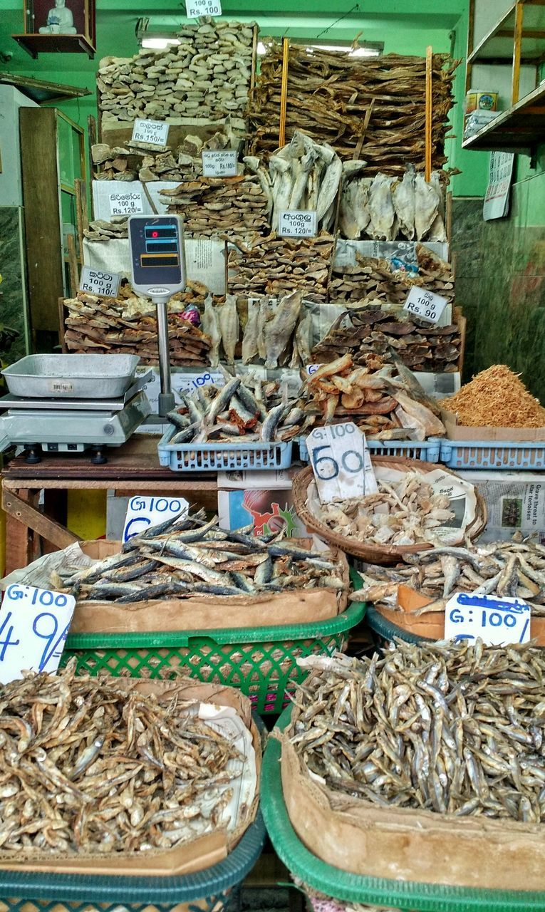 for sale, basket, market, food and drink, text, variation, food, abundance, market stall, retail, large group of objects, grain, dried fish, no people, price tag, day, arrangement, choice, stack, heap, outdoors, healthy eating, freshness, close-up