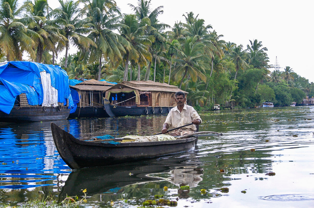 water, nautical vessel, transportation, boat, real people, tree, mode of transport, nature, palm tree, day, outdoors, one person, river, men, moored, full length, beauty in nature, sitting, clear sky, sky, mammal, people