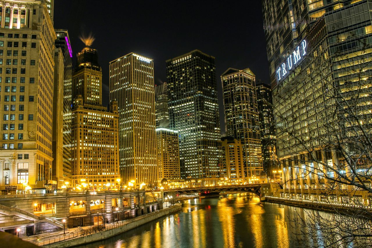 architecture, illuminated, building exterior, night, city, skyscraper, built structure, modern, cityscape, travel destinations, waterfront, no people, outdoors, water, urban skyline, clear sky, sky