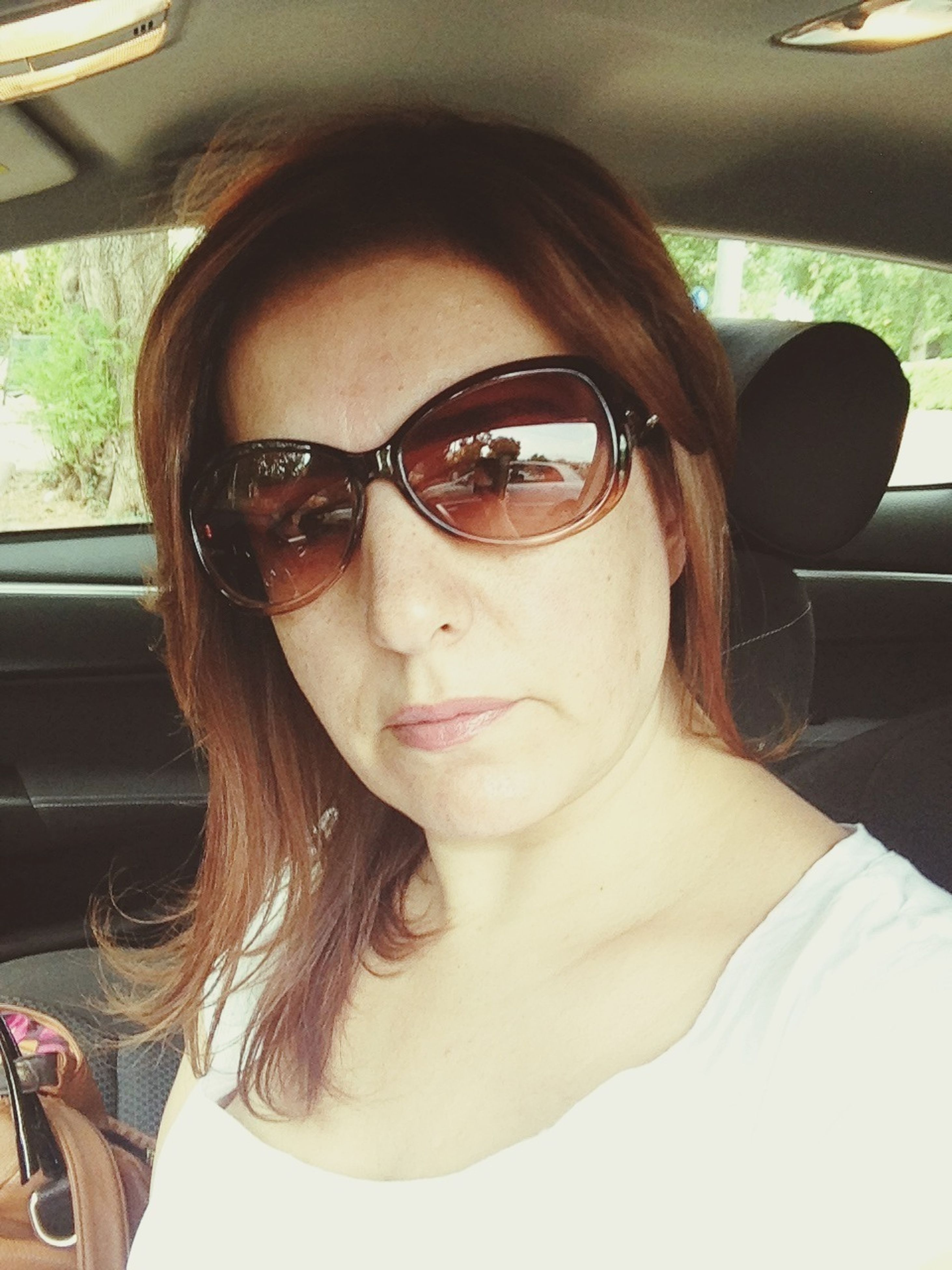portrait, looking at camera, young adult, person, sunglasses, front view, headshot, young women, lifestyles, smiling, car, leisure activity, transportation, vehicle interior, casual clothing, sitting, close-up