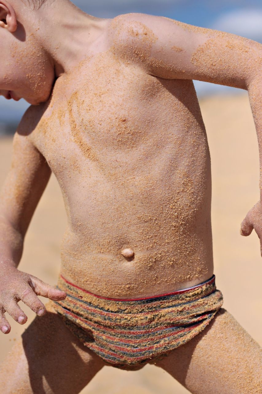 Midsection Of Boy Covered With Sand At Beach