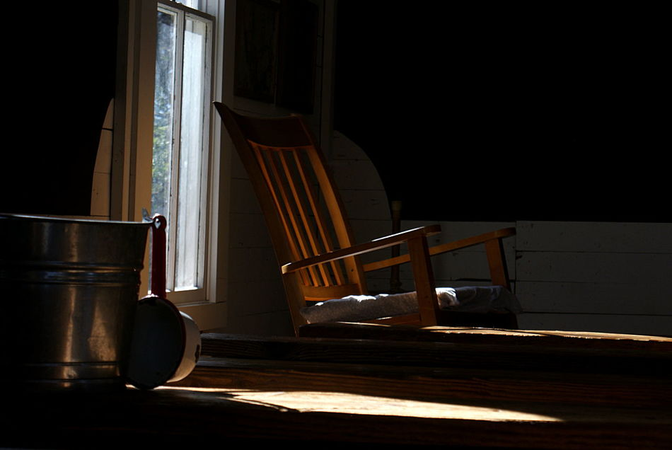 Sun shines through a window into the darkness of an old school house with a rocking chair and metal water bucket. Antique Black Background Darkness Glow History Indoors  Metal Bucket Moody No People Old Fashioned Rocking Chair Room School House Sunlight And Shadow Window Wood - Material