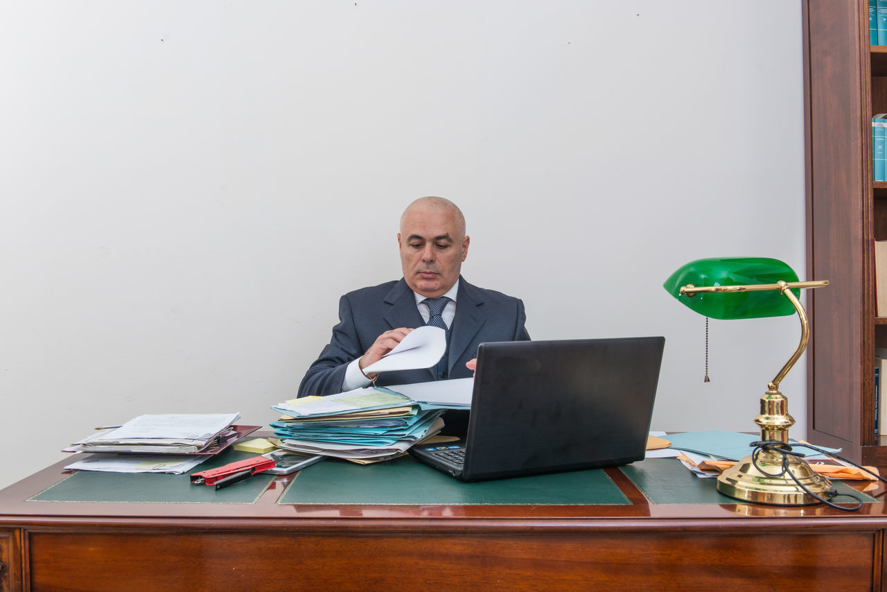 Bill Business Businessman Corporate Business Desk Document Eyeglasses  Finance Front View Hair Loss Indoors  Laptop Men Office One Man Only One Person Only Men Paperwork Portrait Shaved Head Sitting Technology Using Laptop Wireless Technology Working