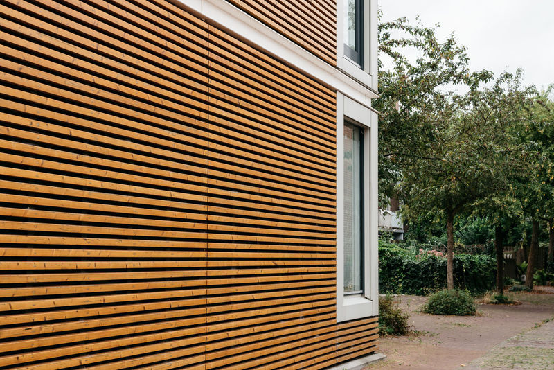 Modern architecture facade with lining of wood slats Architecture Building Exterior Built Structure Close-up Construction Corrugated Iron Day House Minimalism Minimalist Minimalist Architecture Modern Architecture No People Outdoors Pipe - Tube Residential Building Shutter Slats Sustainability Tree Wooden Wooden Slats