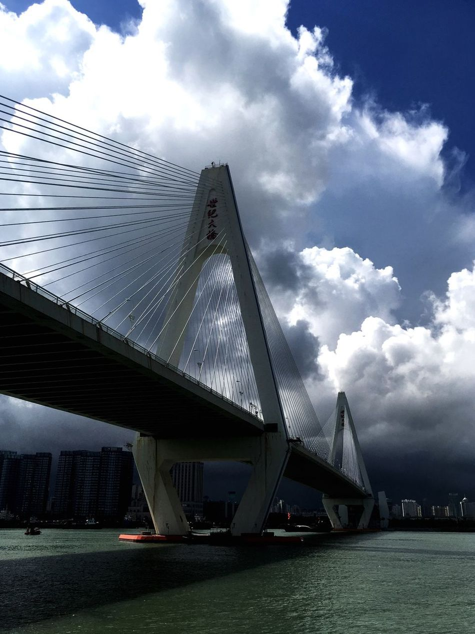 EyeEmNewHere Bridge - Man Made Structure Architecture Engineering Connection Built Structure Sky Cloud - Sky Suspension Bridge Transportation Travel Destinations Bridge Travel Outdoors City Low Angle View Day No People Water Modern Building Exterior