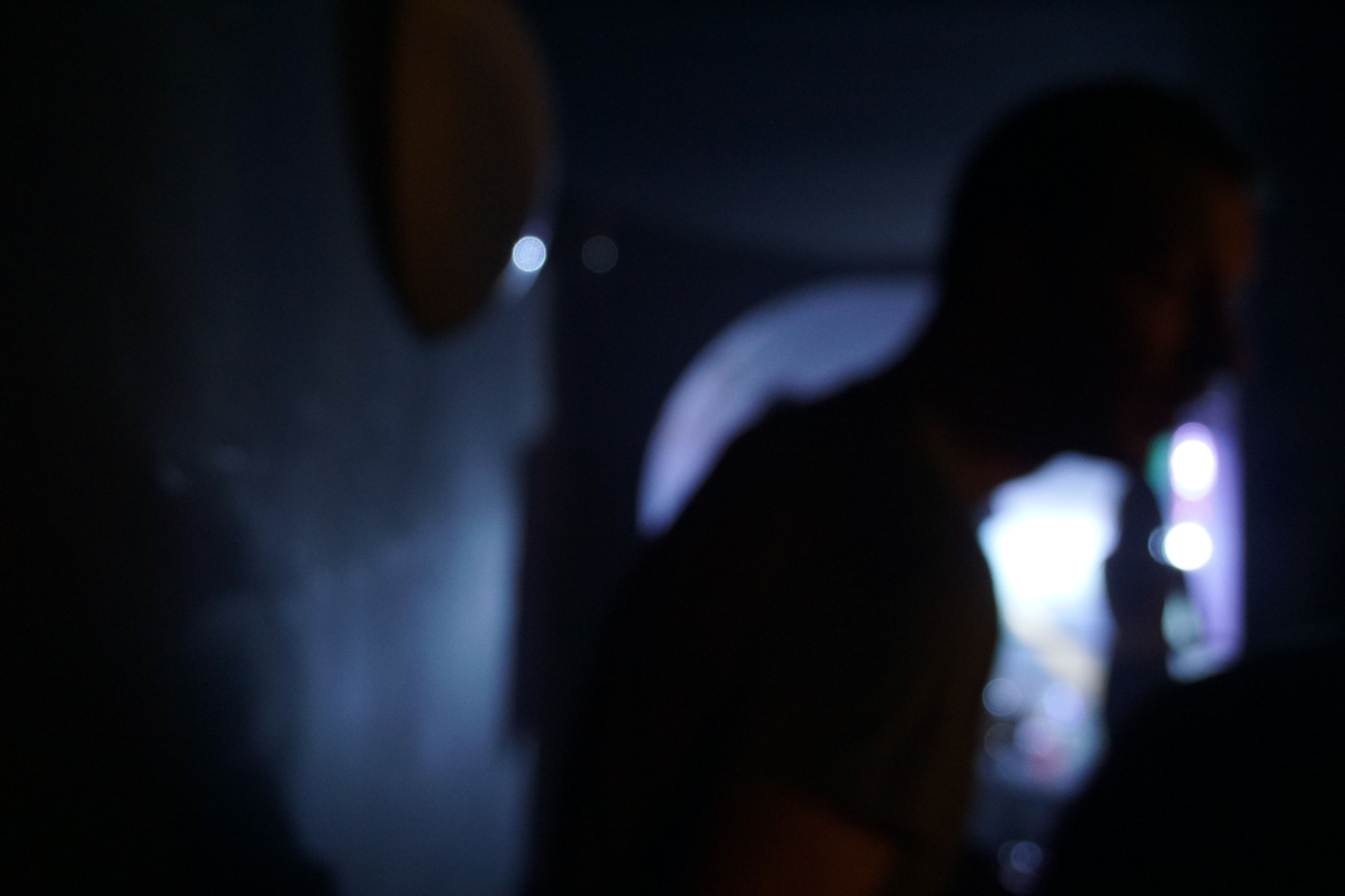 men, lifestyles, night, illuminated, leisure activity, silhouette, rear view, person, focus on foreground, standing, defocused, unrecognizable person, indoors, dark, lighting equipment, selective focus, holding