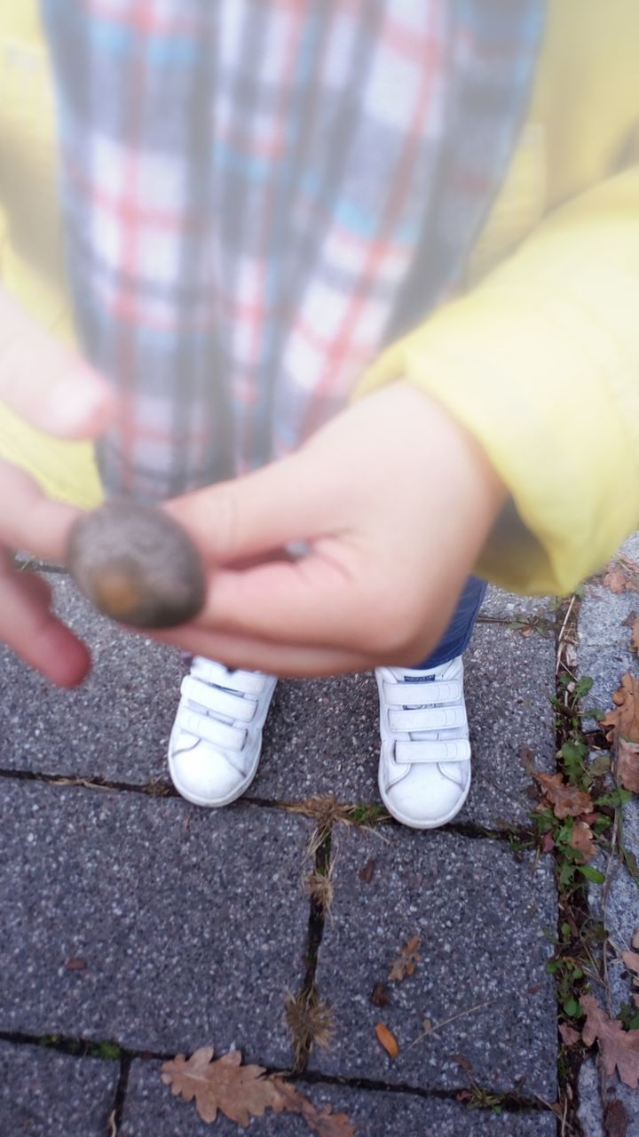 one person, childhood, day, real people, outdoors, boys, child, human body part, human hand, close-up, low section, playing, people
