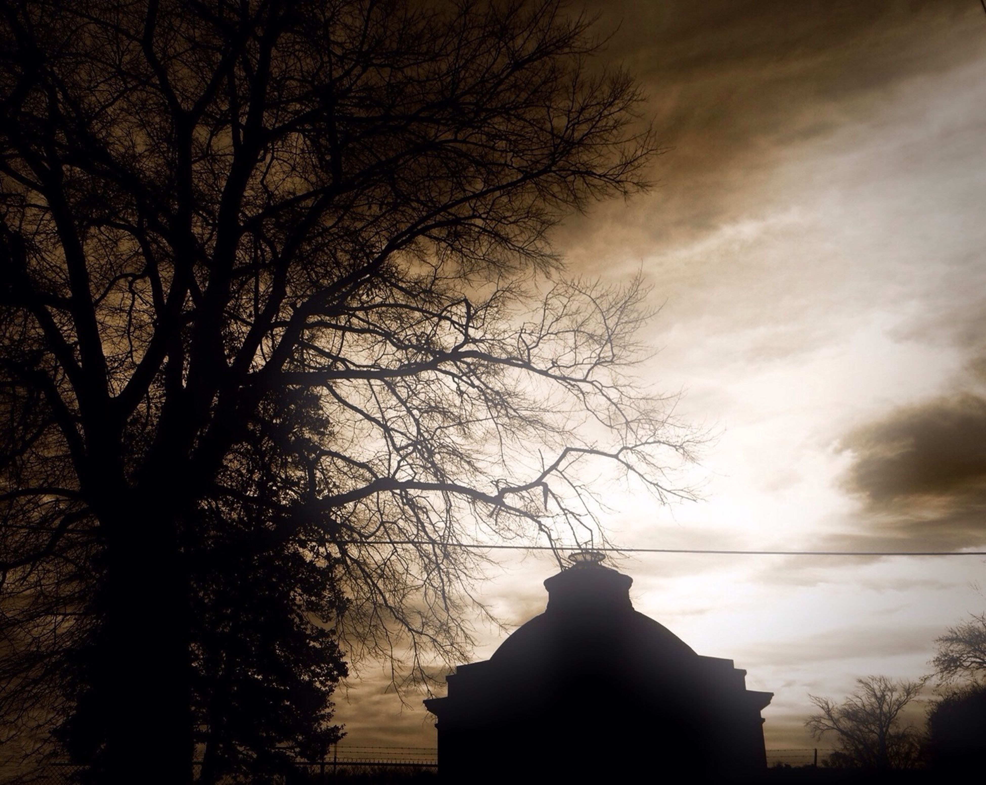 tree, silhouette, bare tree, sky, branch, sunset, cloud - sky, built structure, low angle view, architecture, building exterior, dusk, nature, tranquility, cloudy, cloud, beauty in nature, outdoors, spirituality, no people